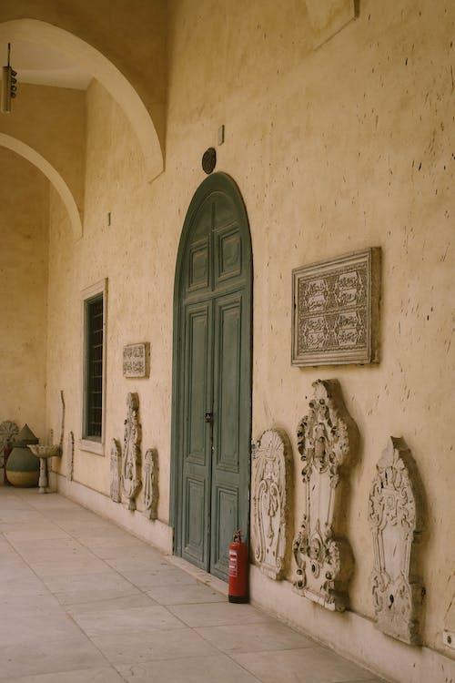 Grey Wooden Door Between Beige Concrete Wall