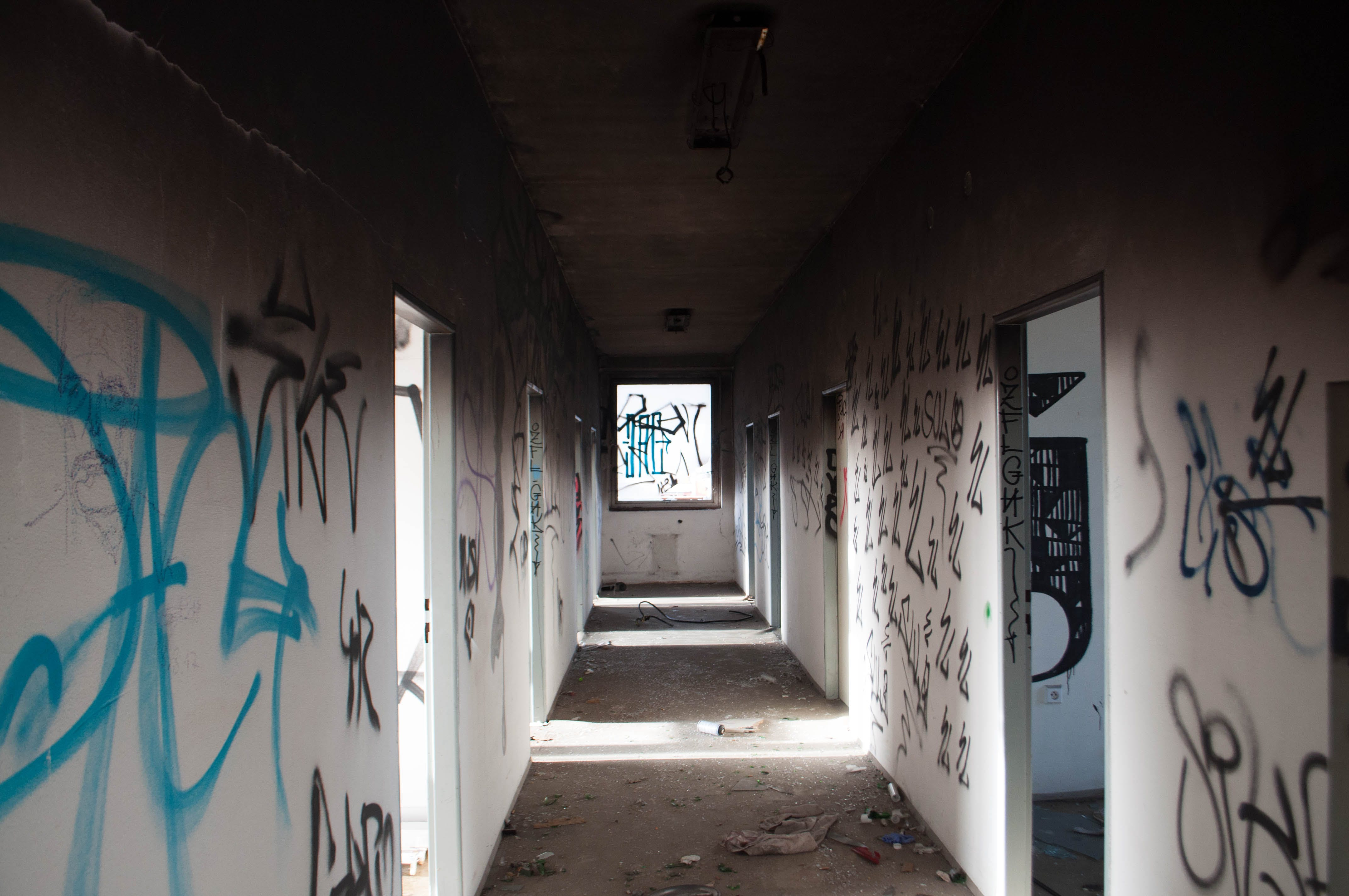 Empty Hallway With Black and Blue Graffiti
