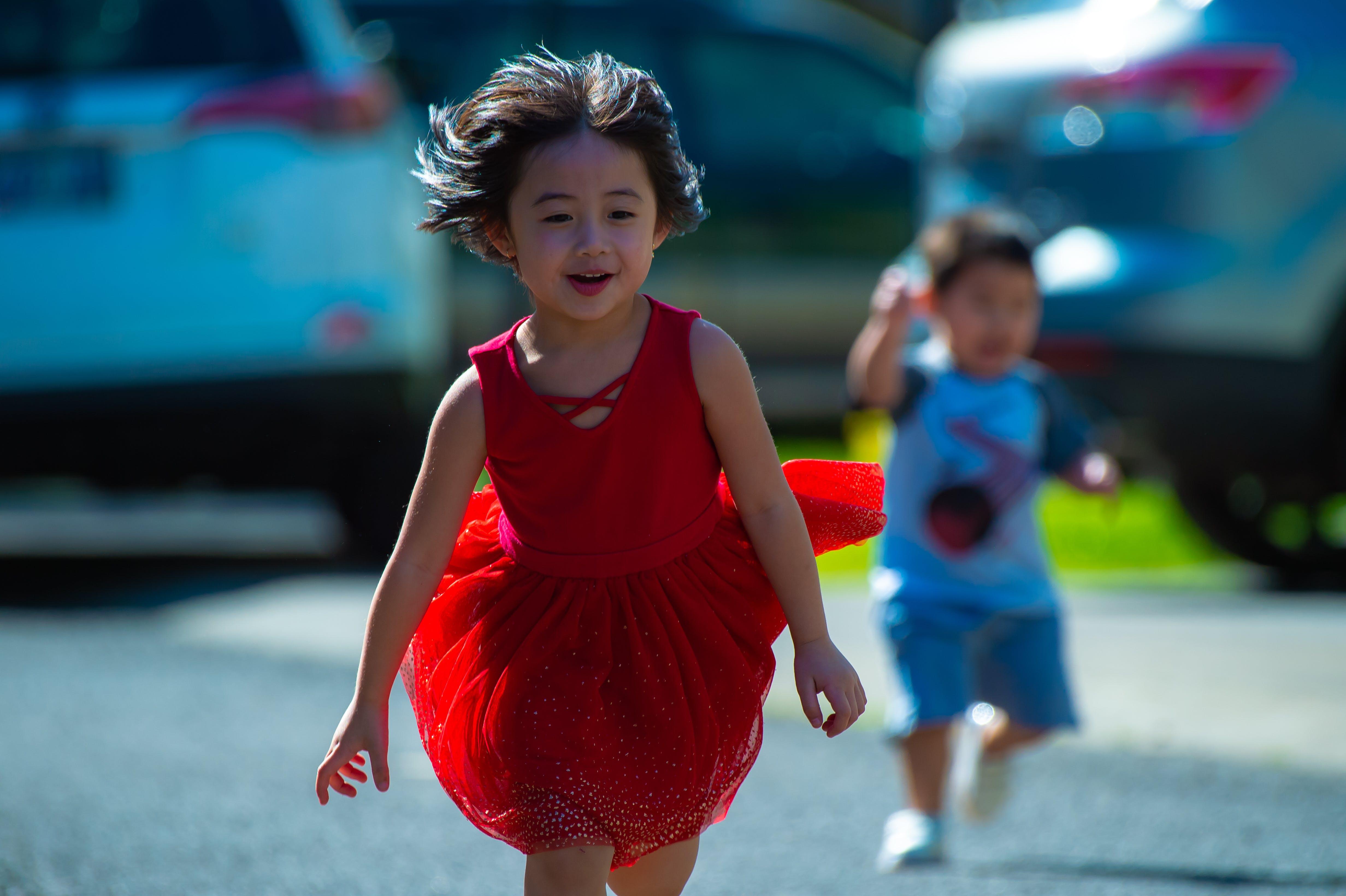 Photo of Girl in Red Dress Running on Street