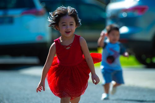 Photo of Girl in Red Dress Running on Street