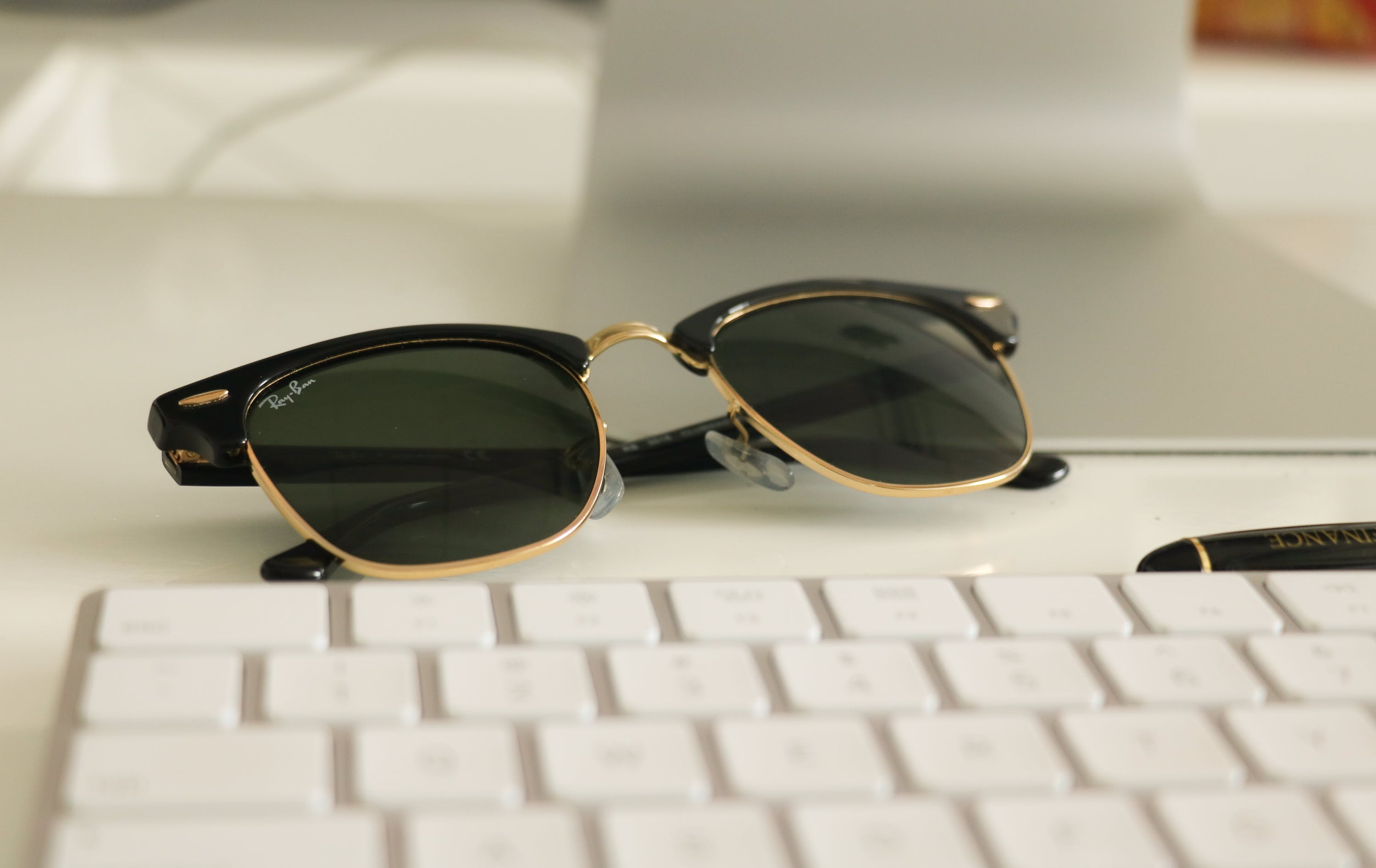 Black Ray-ban Clubmaster Sunglasses on White Surface