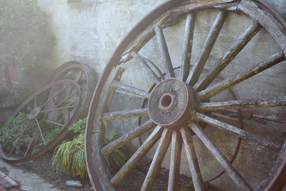 Серое многоспицевое колесо, прислоненное к стене