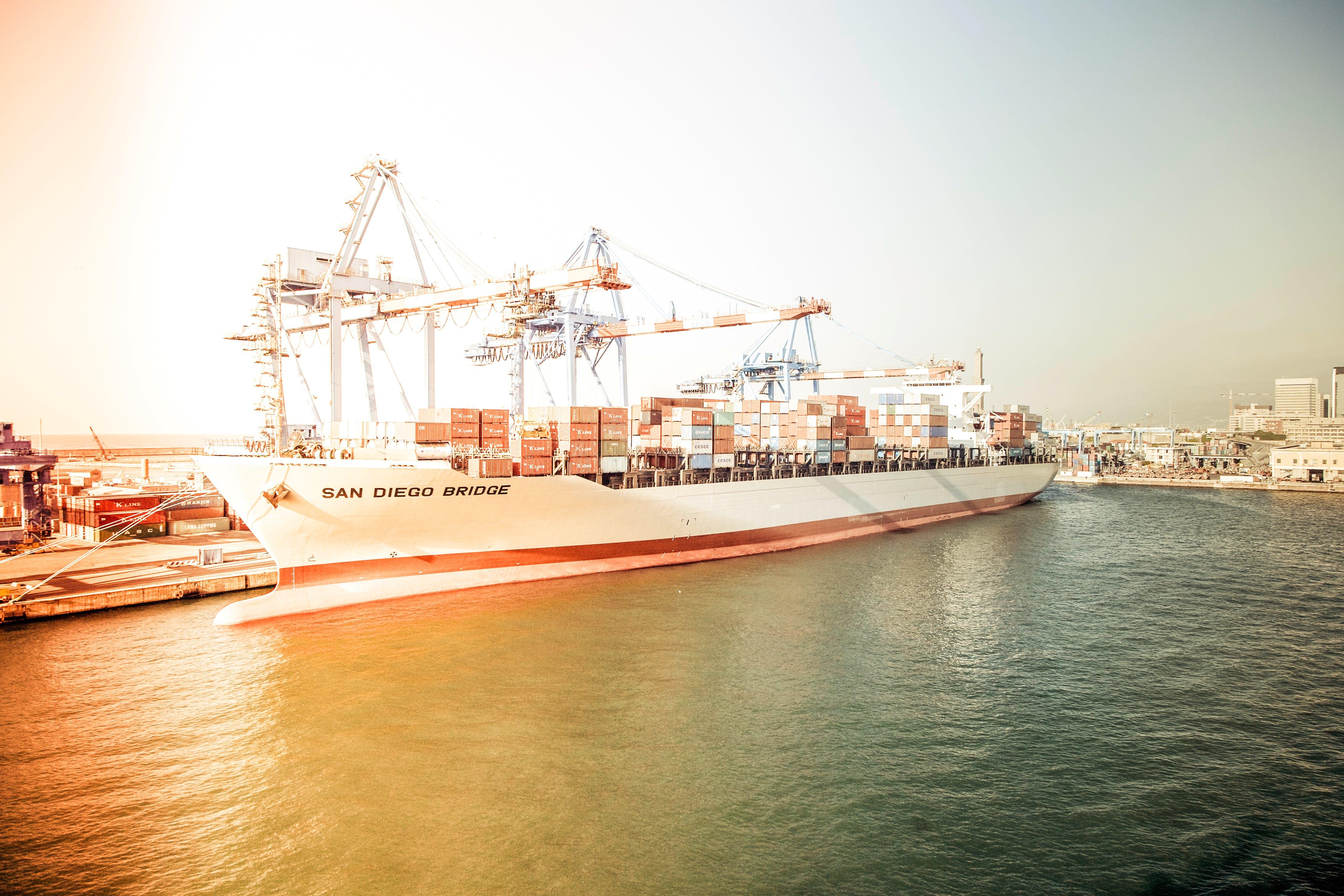 White and Orange Cargo Ship Docking during Daytime