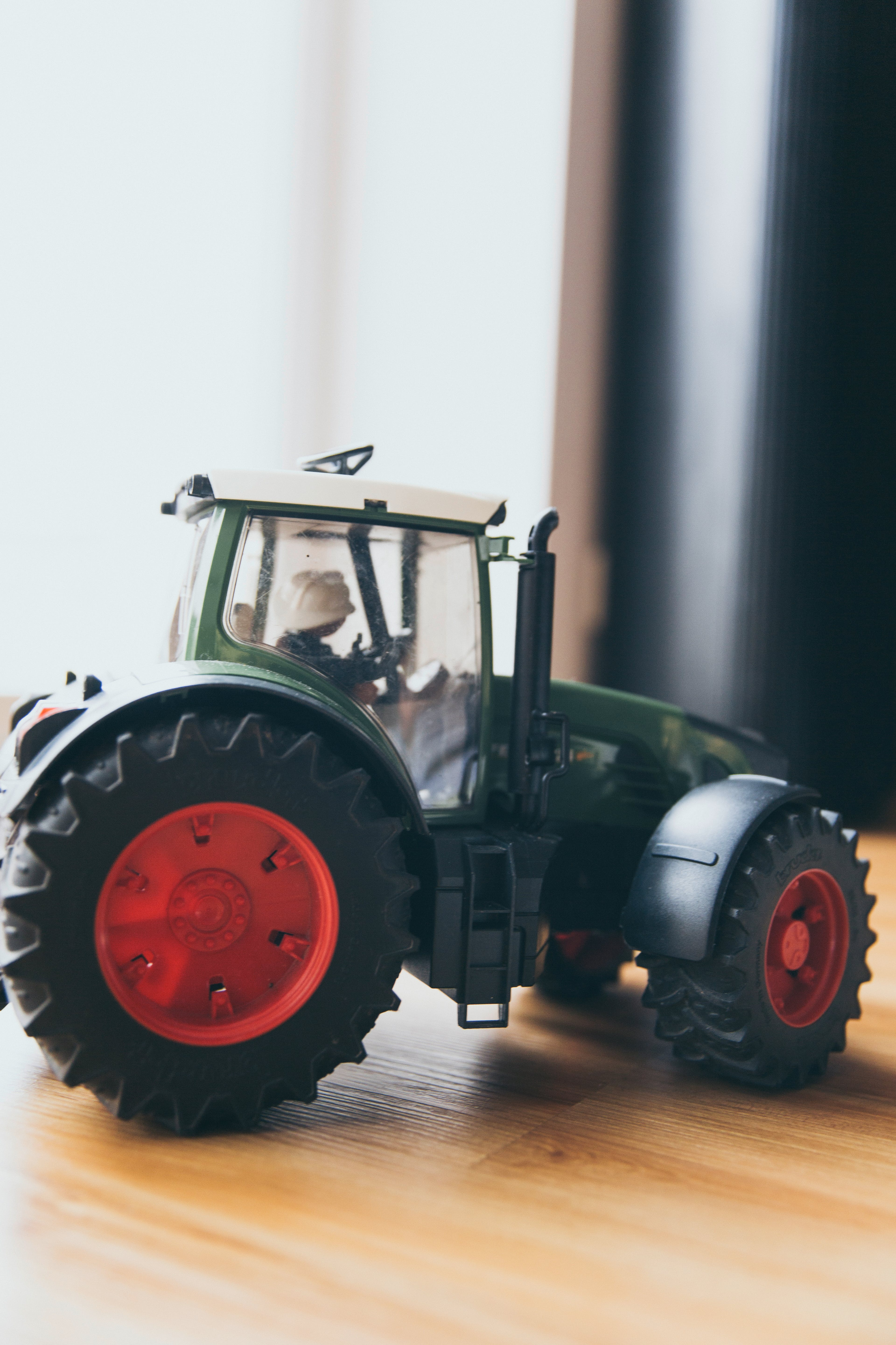 Black and Green Farm Tractor Toy on Brown Wooden Table Beside Window