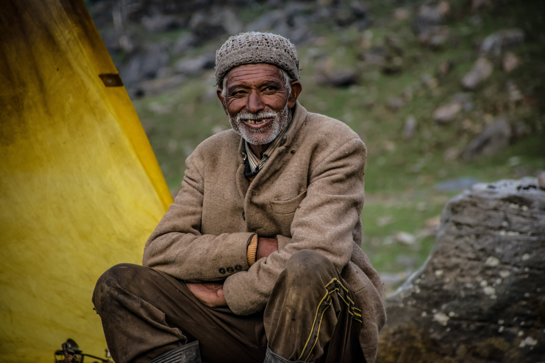 Smiling Man Wearing Gray Knit Cap Sitting Near Gray Rock