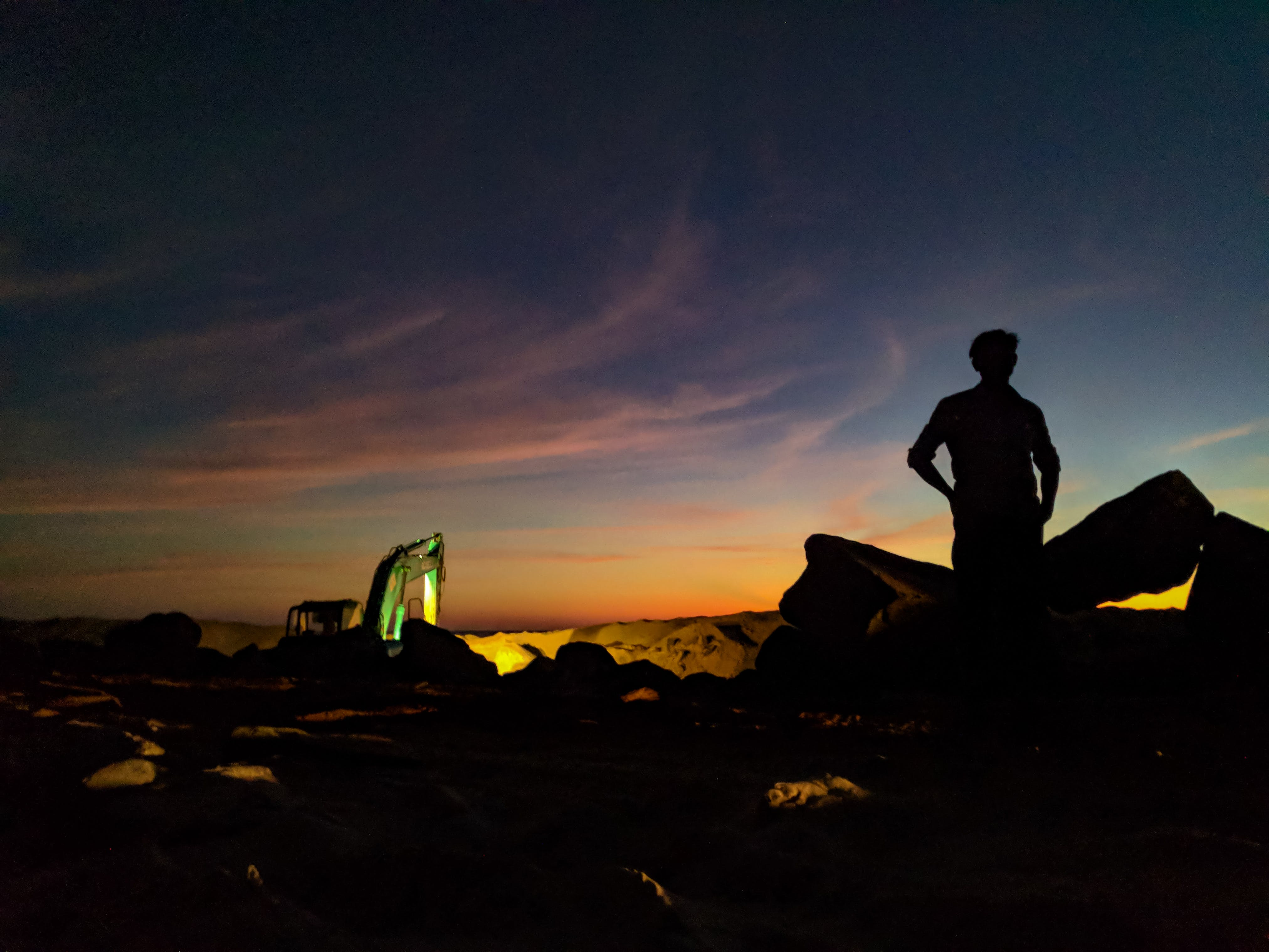 Silhouette Photo of Person Standing Near the Rock