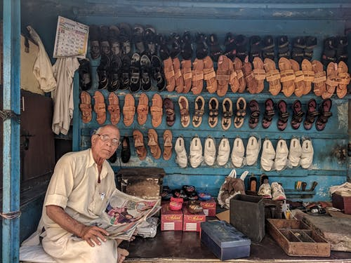 Man Reading Newspaper Surrounded by Shoes