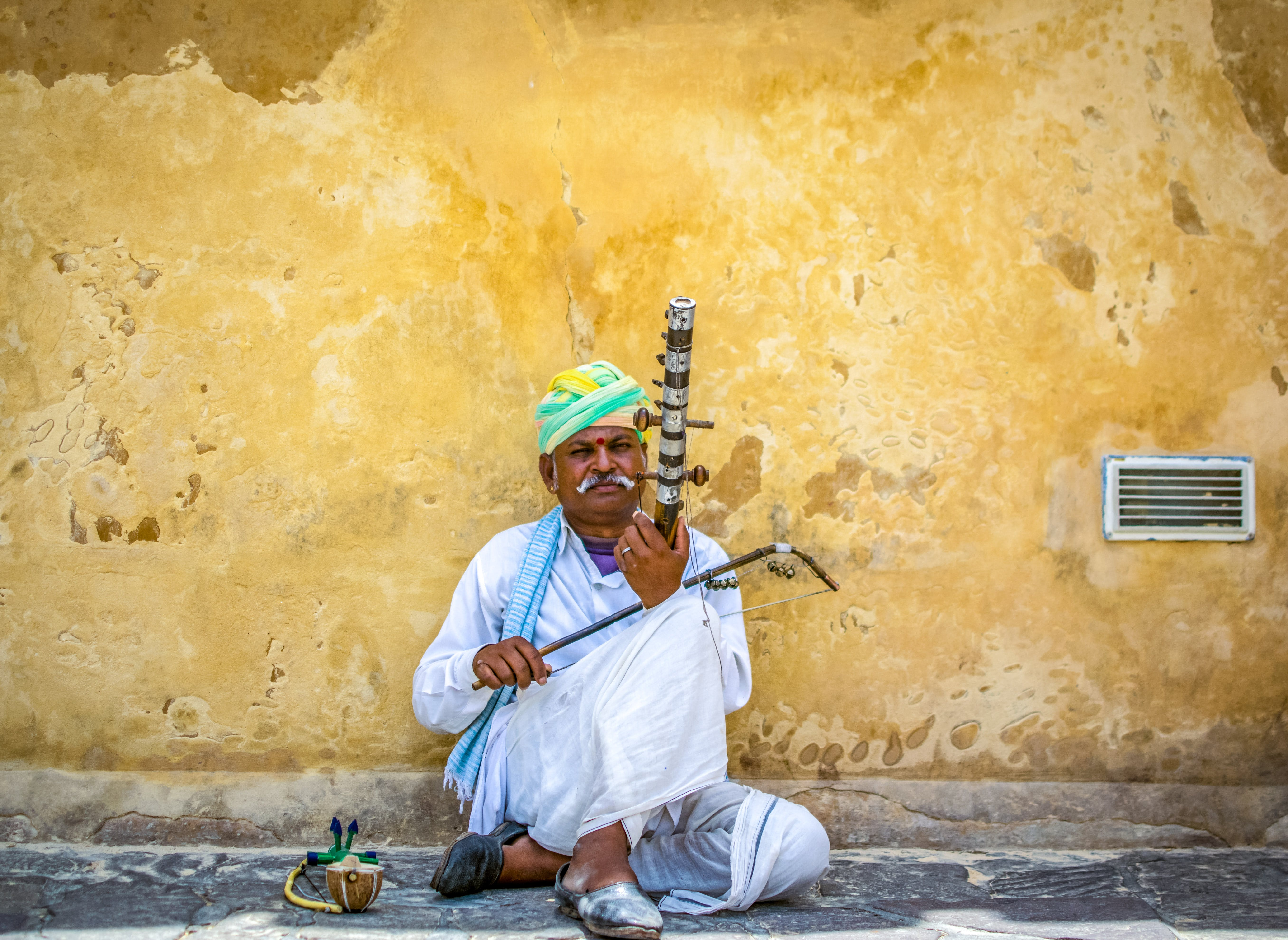 Man Holding String Instrument While Sitting on Concrete Pavement