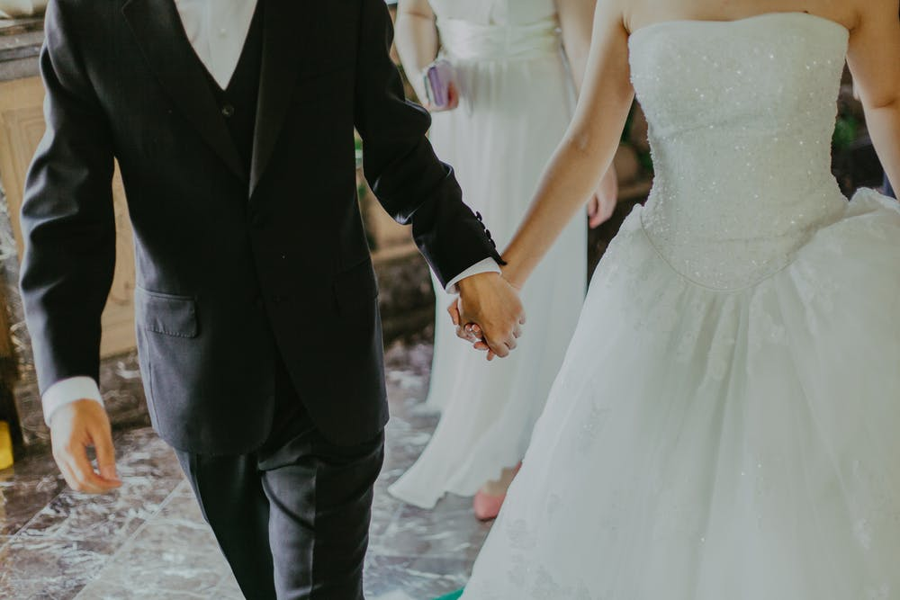 Bride and groom holding hands while walking. | Photo: Pexels
