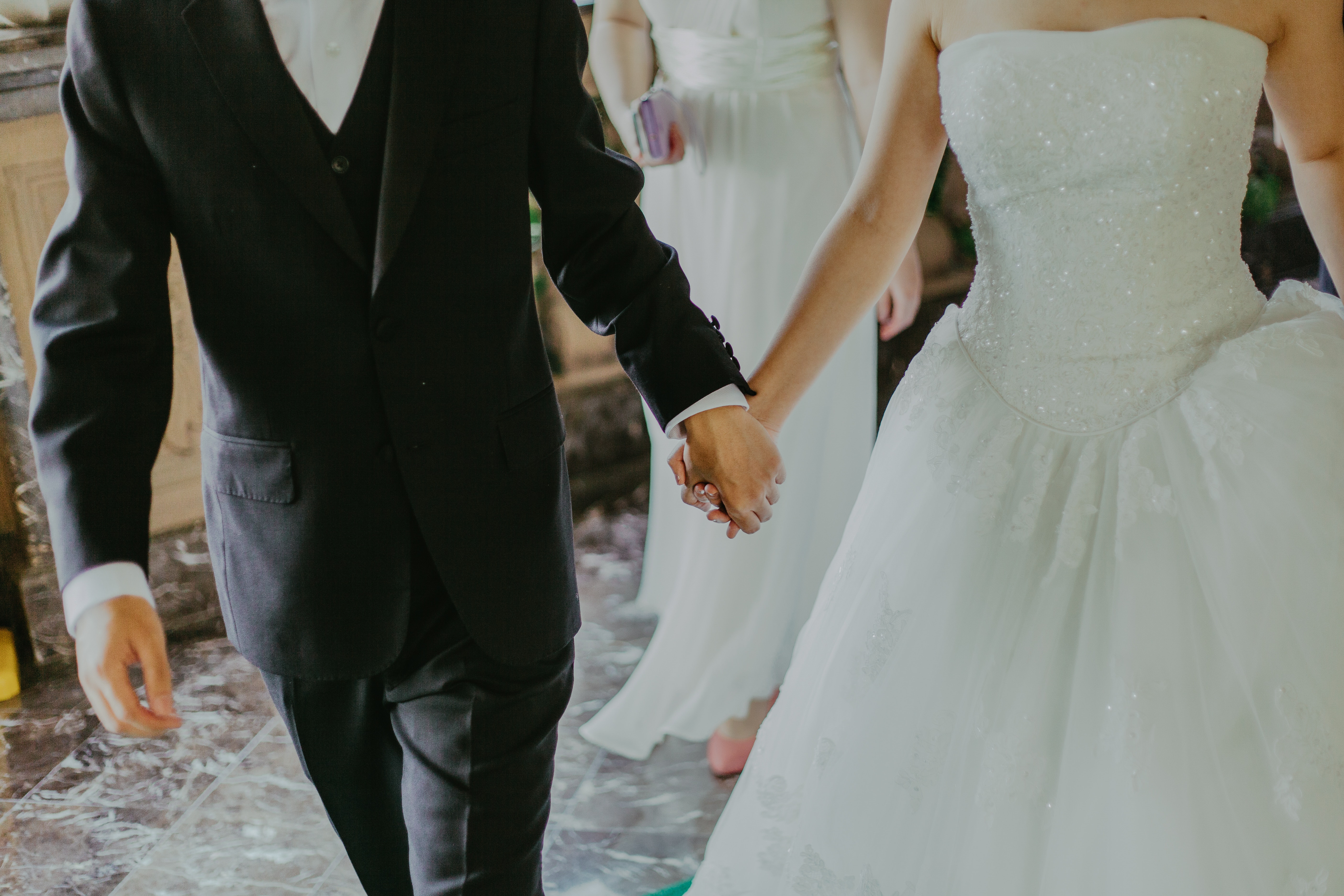 Woman Wearing White Wedding Gown Holding Hands With Man While Walking Free Stock Photo