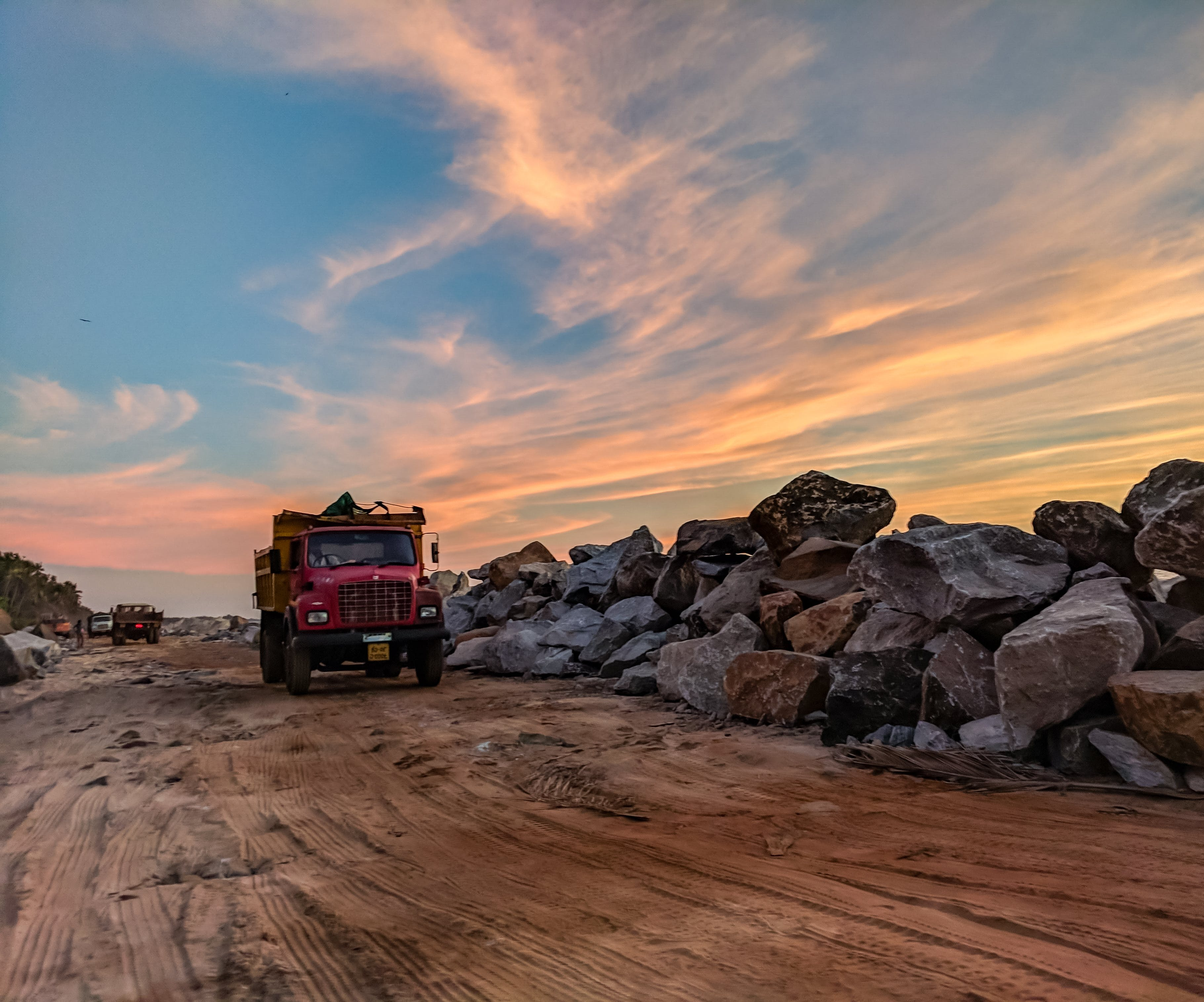 Red Dump Truck Near Filed Rocks Under Cloudy Sky