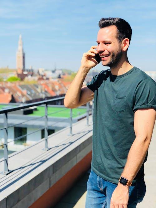 Man Wearing Black Crew-neck Shirt Holding Mobile Phone