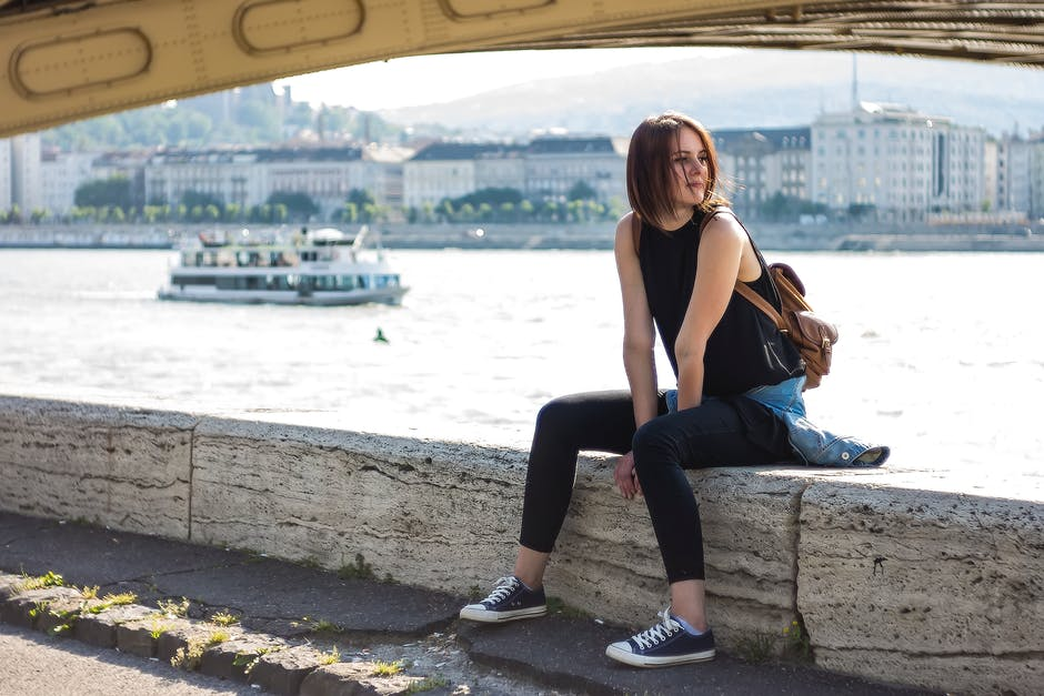 Woman in Black Tank Top and Black Leggings Sitting at Daytime