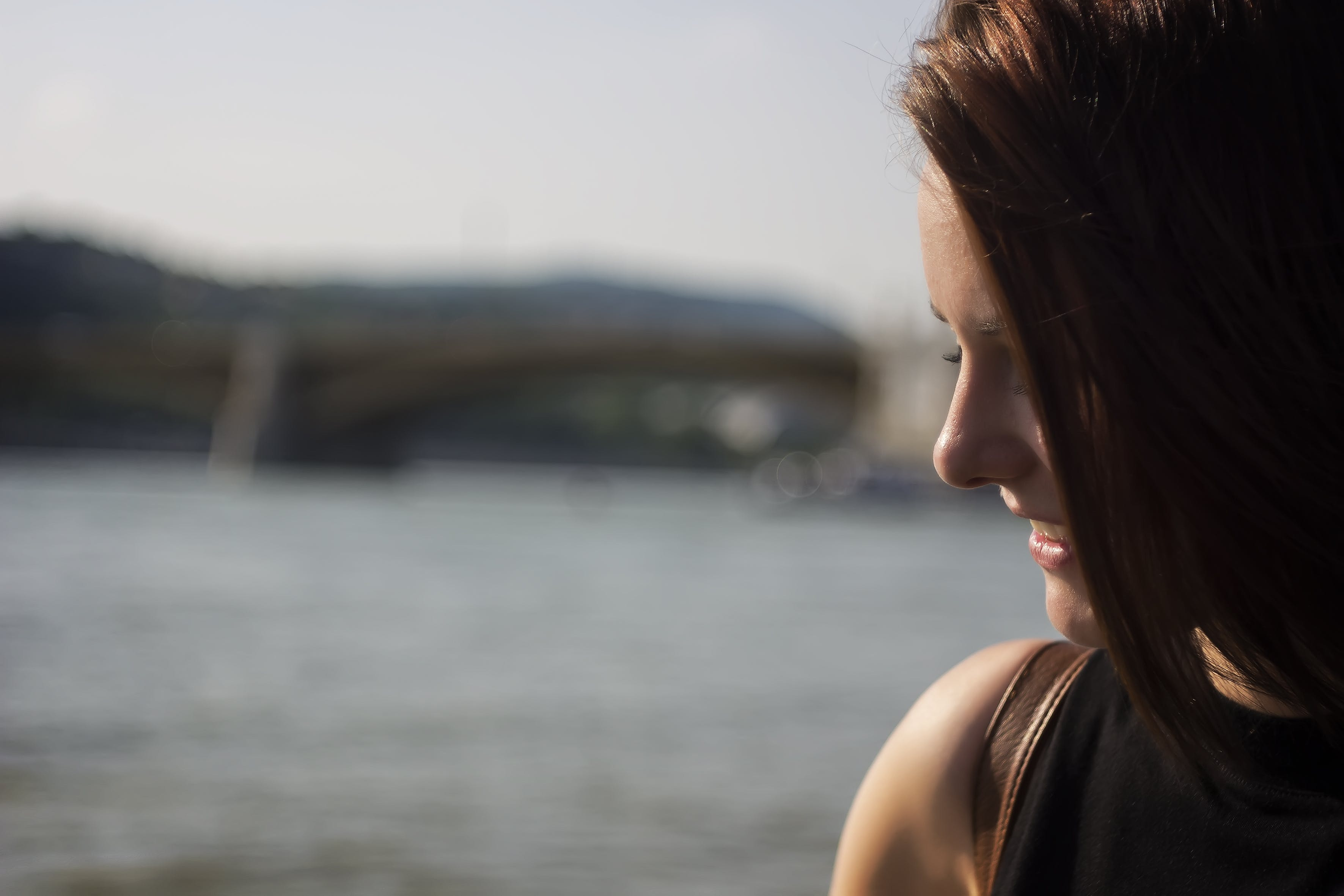 Close Up Photography of Side View Angle of a Woman Smiling Near Seawater during Daytime