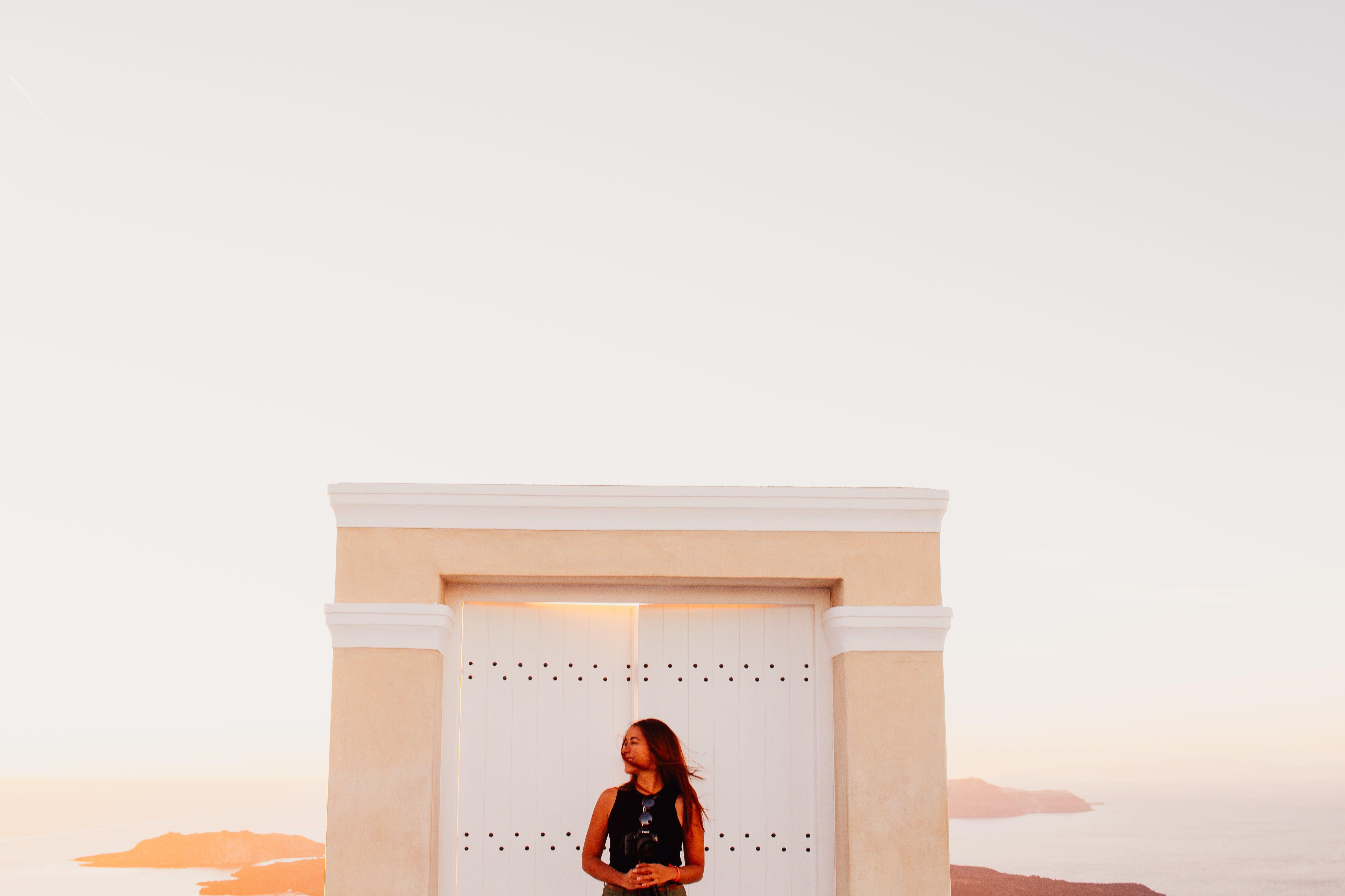 Woman Wearing Black Sleeveless Top Posing in Front of White Wooden Door
