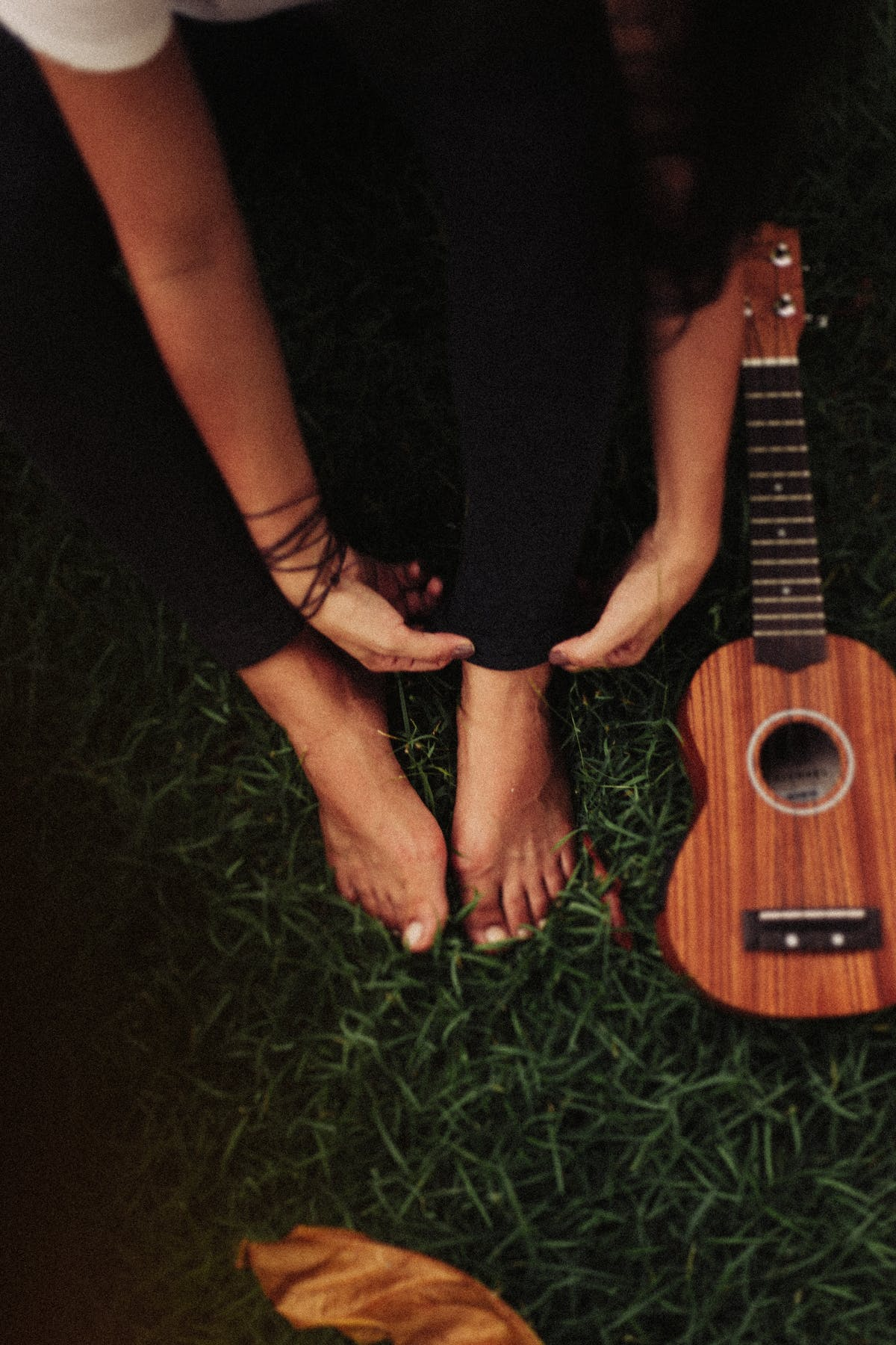 Person Sitting on Green Grass Field Beside Ukulele