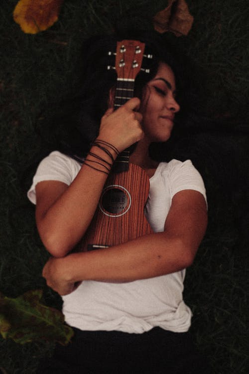 Person Hugging Brown Ukelele