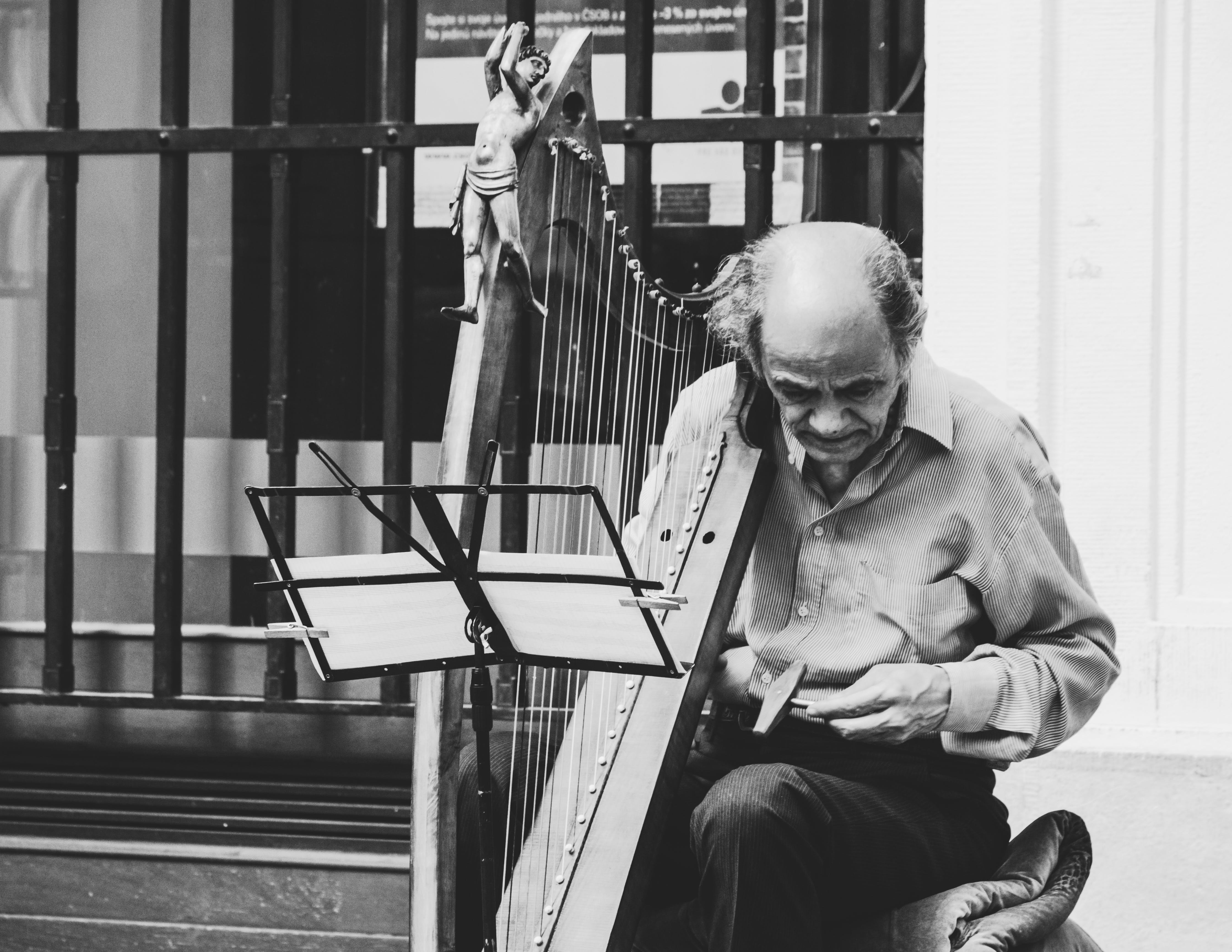 Greyscale Photo of Man Holding Harp