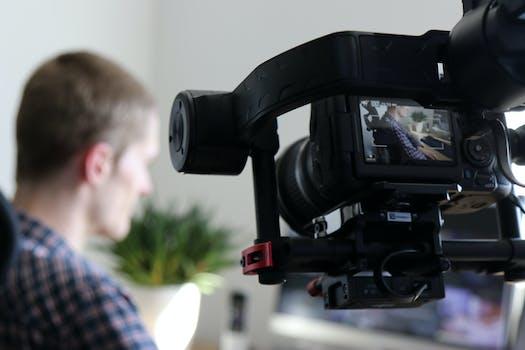 Black Video Camera Turn on Next to Man Wears Black and Gray Shirt