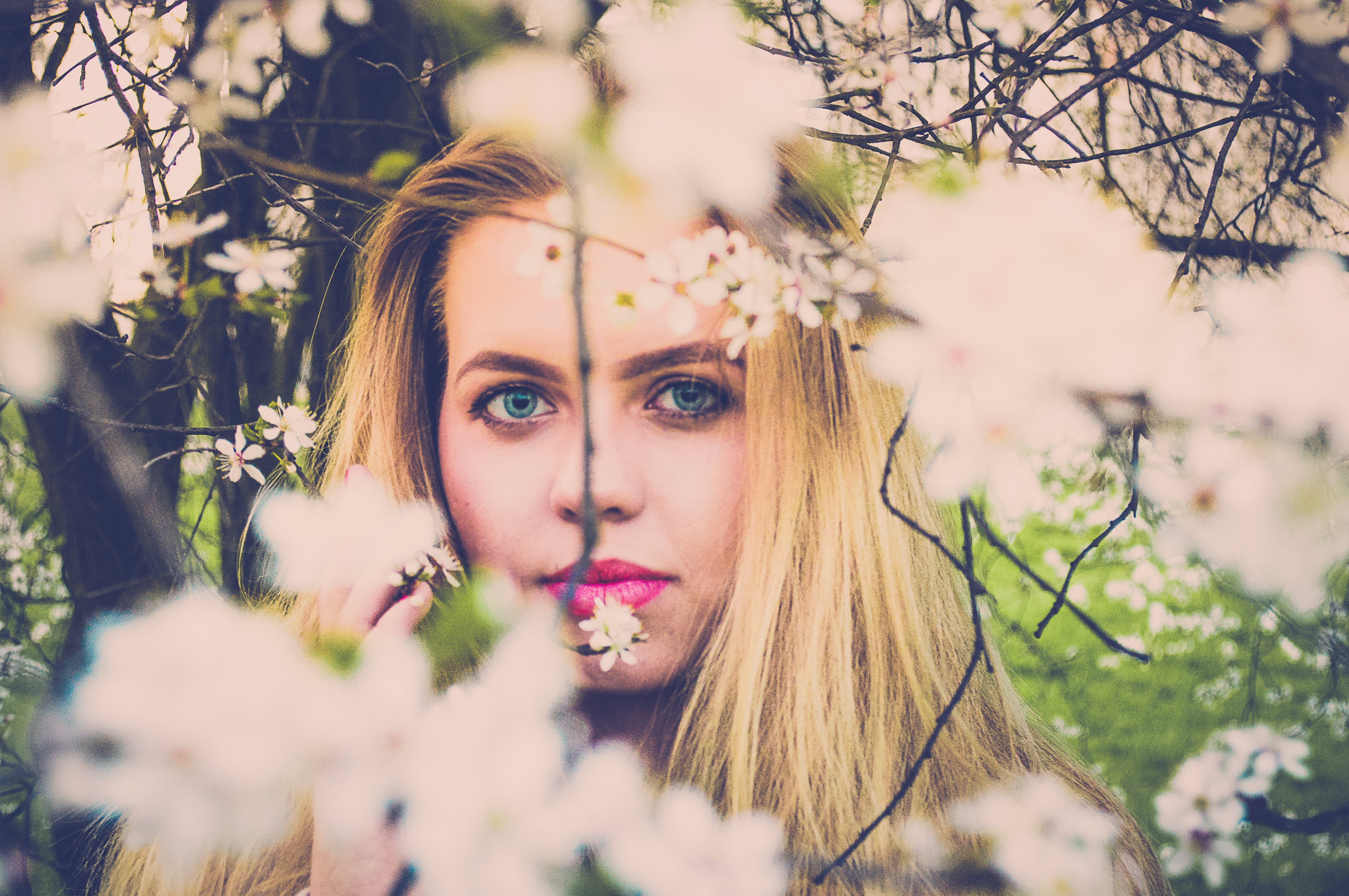 Woman With Pink Lipsticks and Blonde Taking Photo With White Petaled Flowers