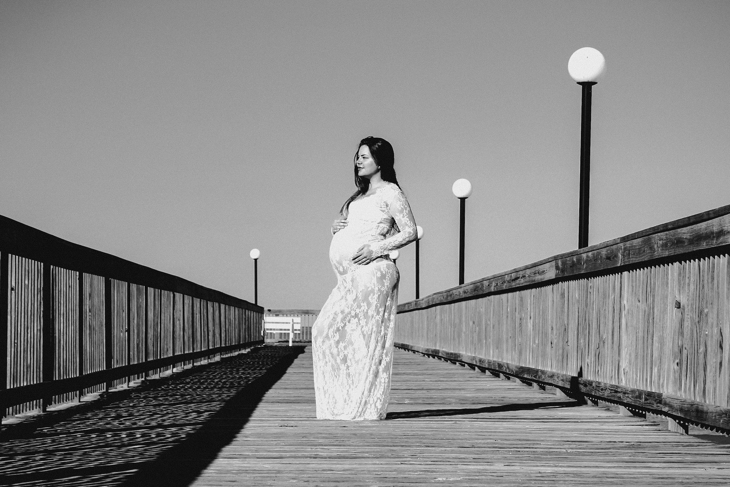 Grayscale Photo of Pregnant Woman Wearing Maxi Dress