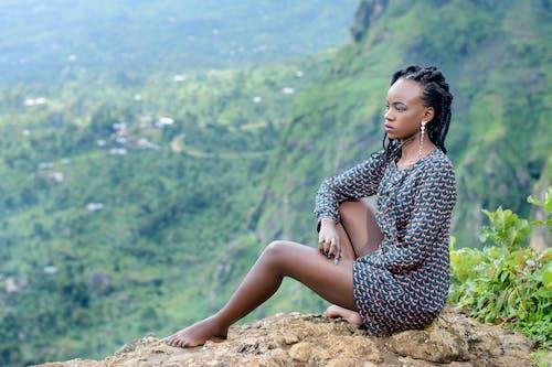 Woman Sitting on Ground Near Mountain