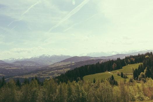 Green Grass Behind Brown Mountain Under White Sky