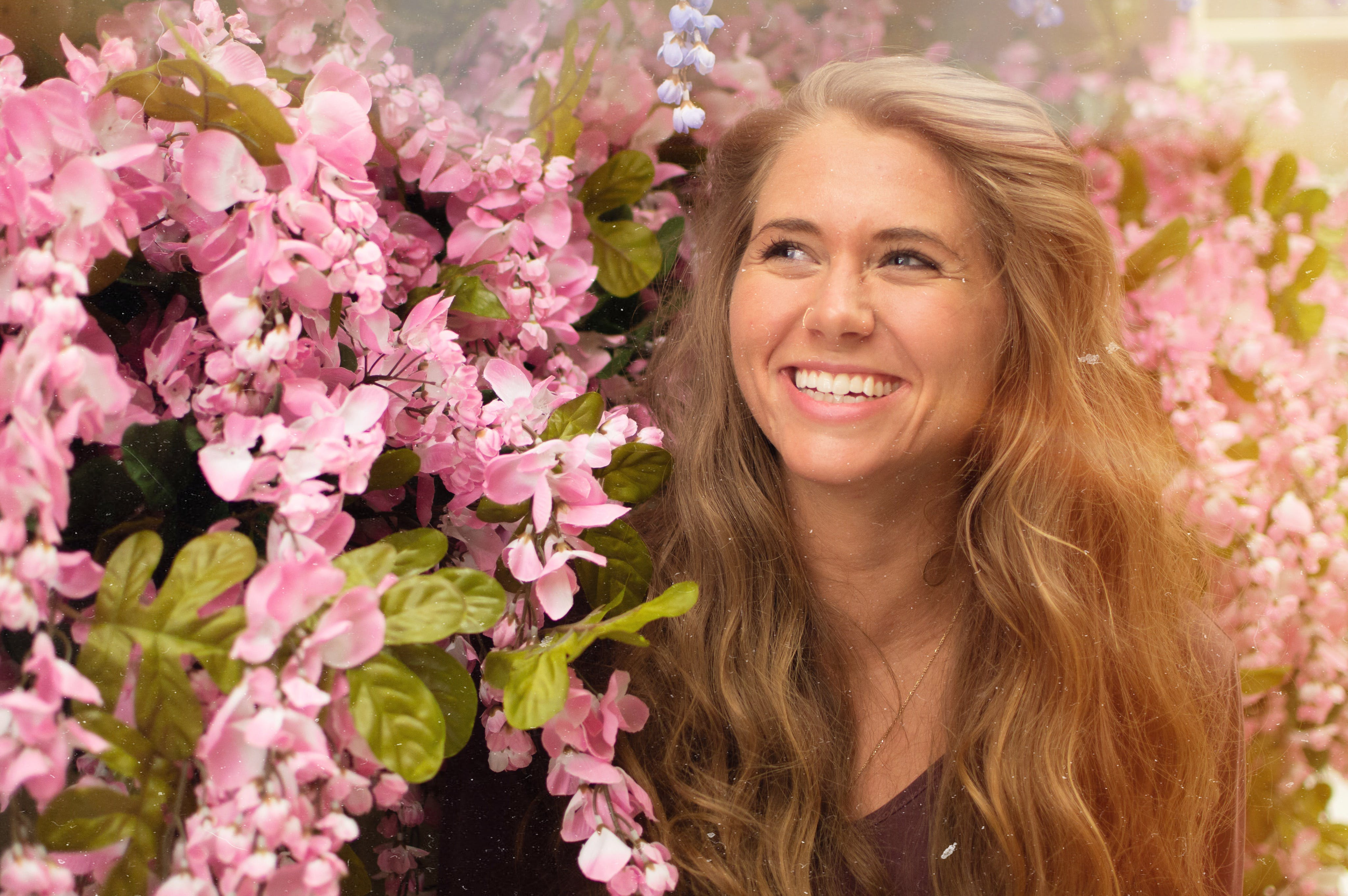 Photo of Woman Standing Beside Pink Flowers