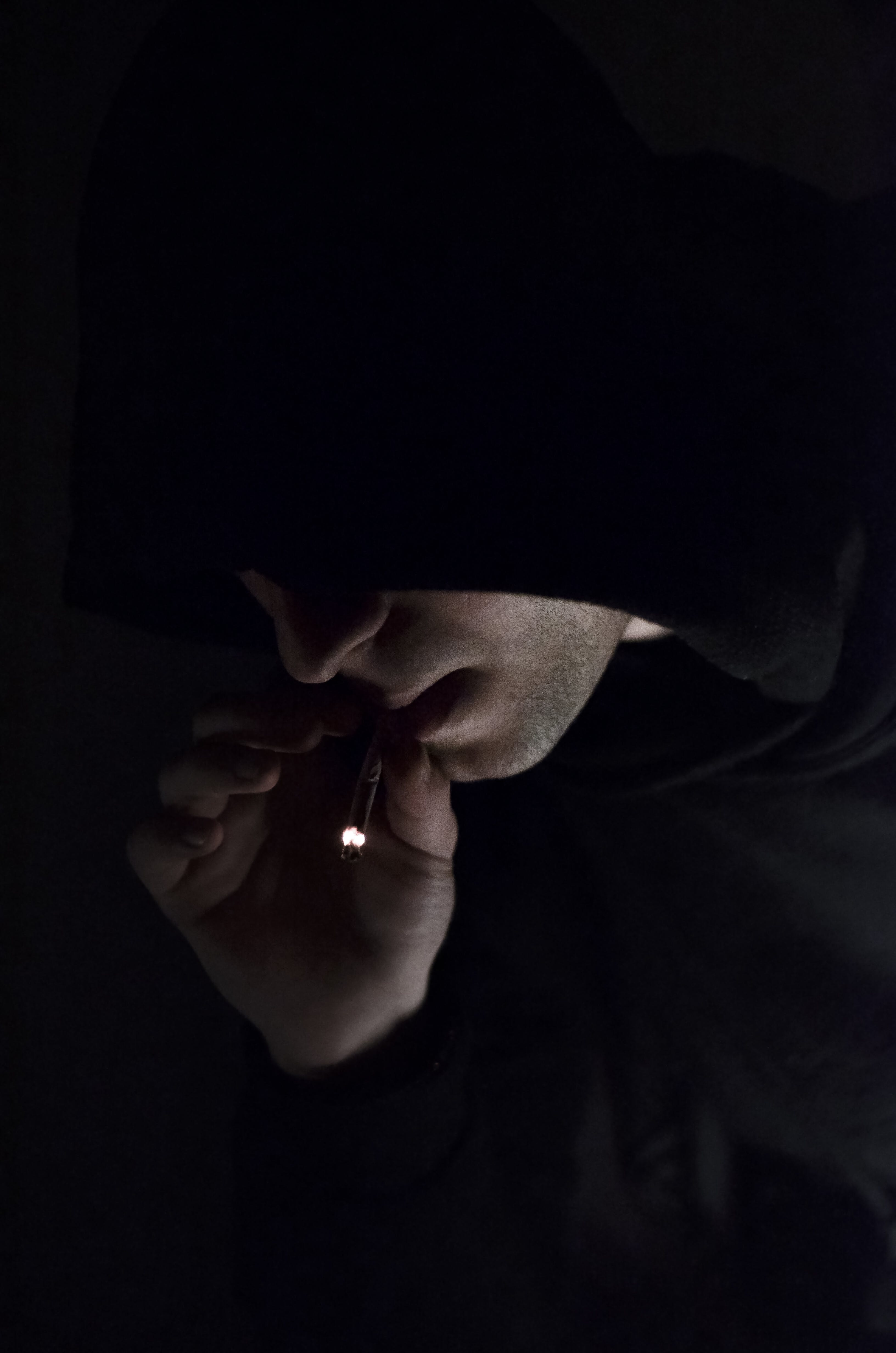 Man in Hoodie Smoking Cigarette