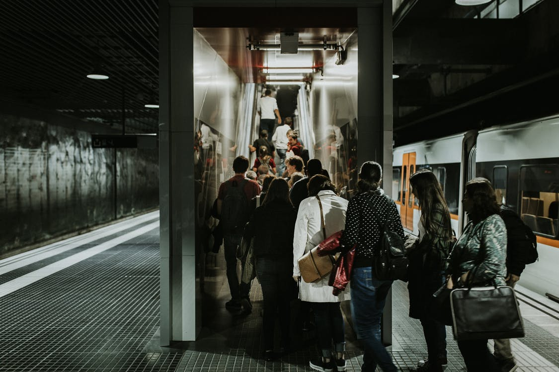 Grayscale Photography of People Falling in Line at Train Station