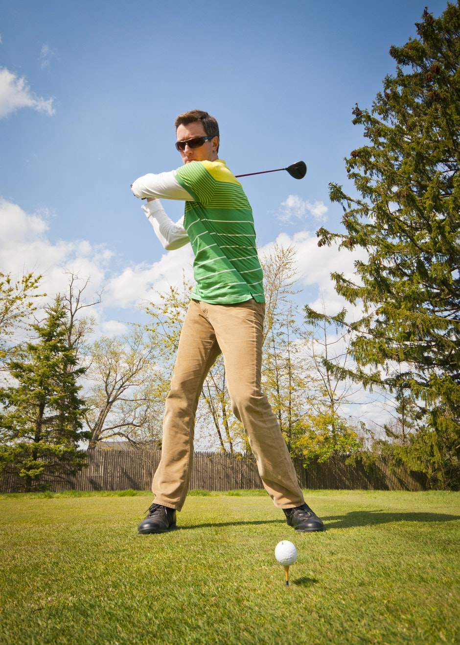 Man in Green and White Stripes Long Sleeve Shirt Holding Black Golf Club