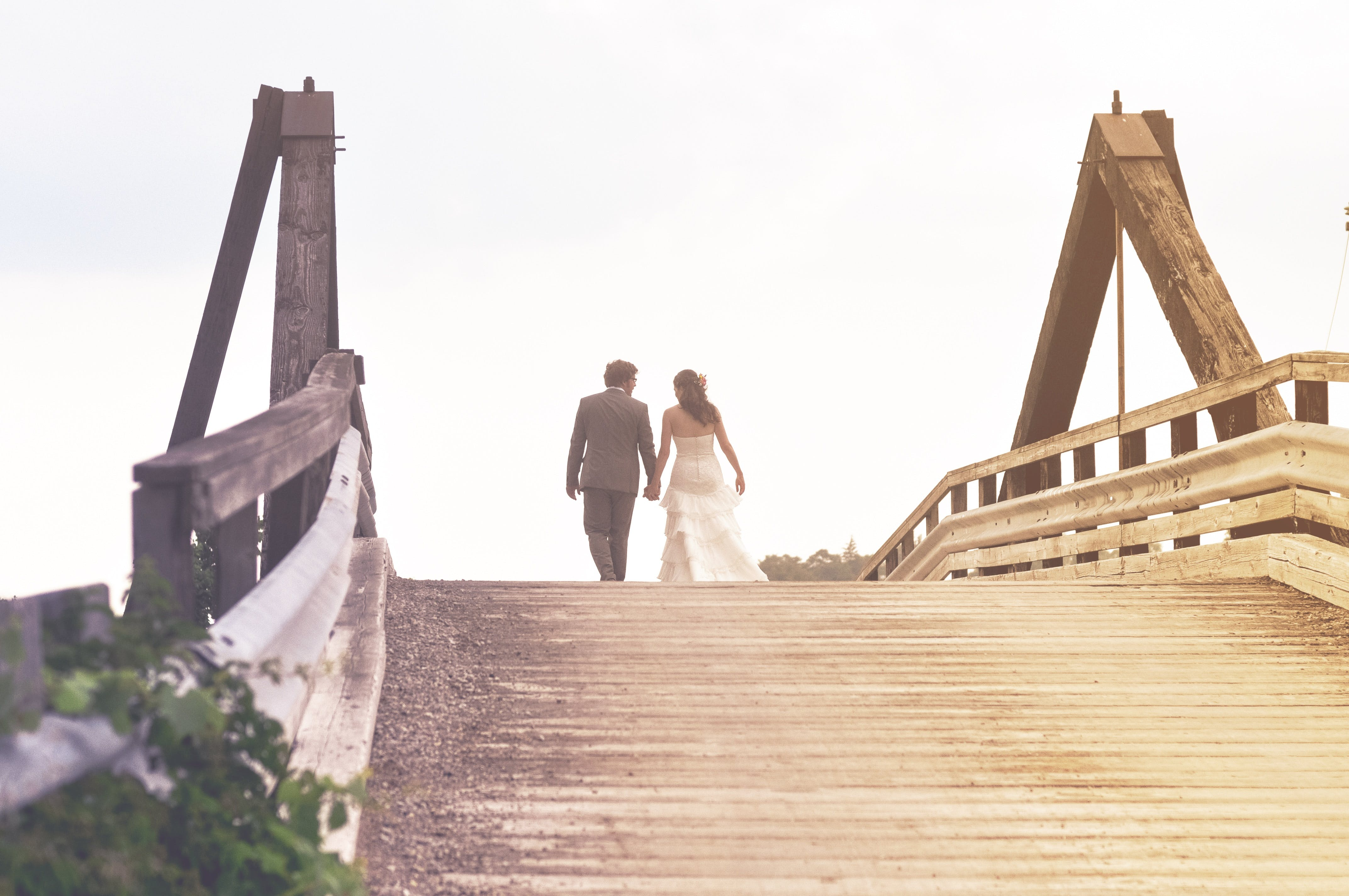Man and Woman Holding Hands While Walking on Bridge