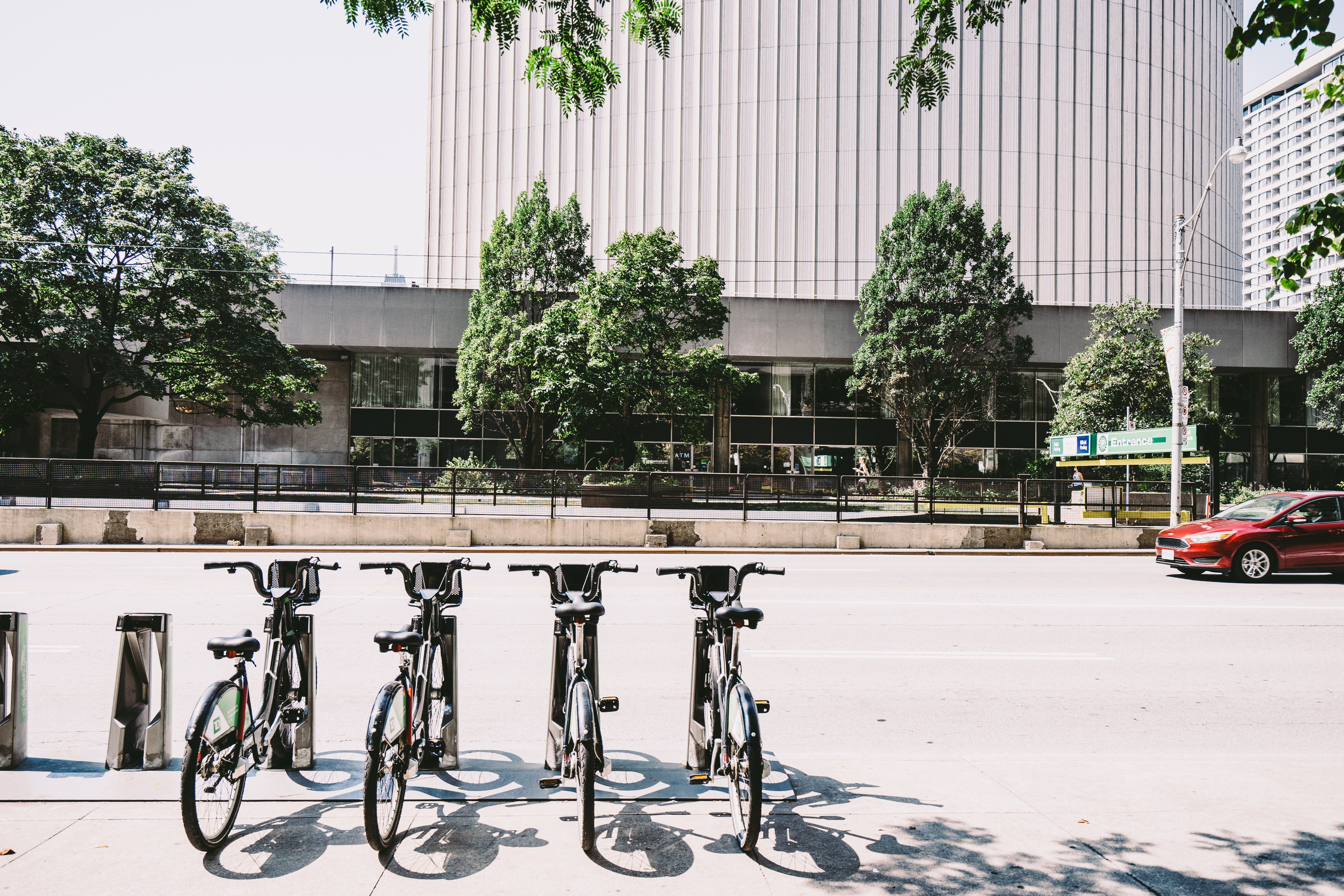 Four Black Parked Bicycles Near the Road