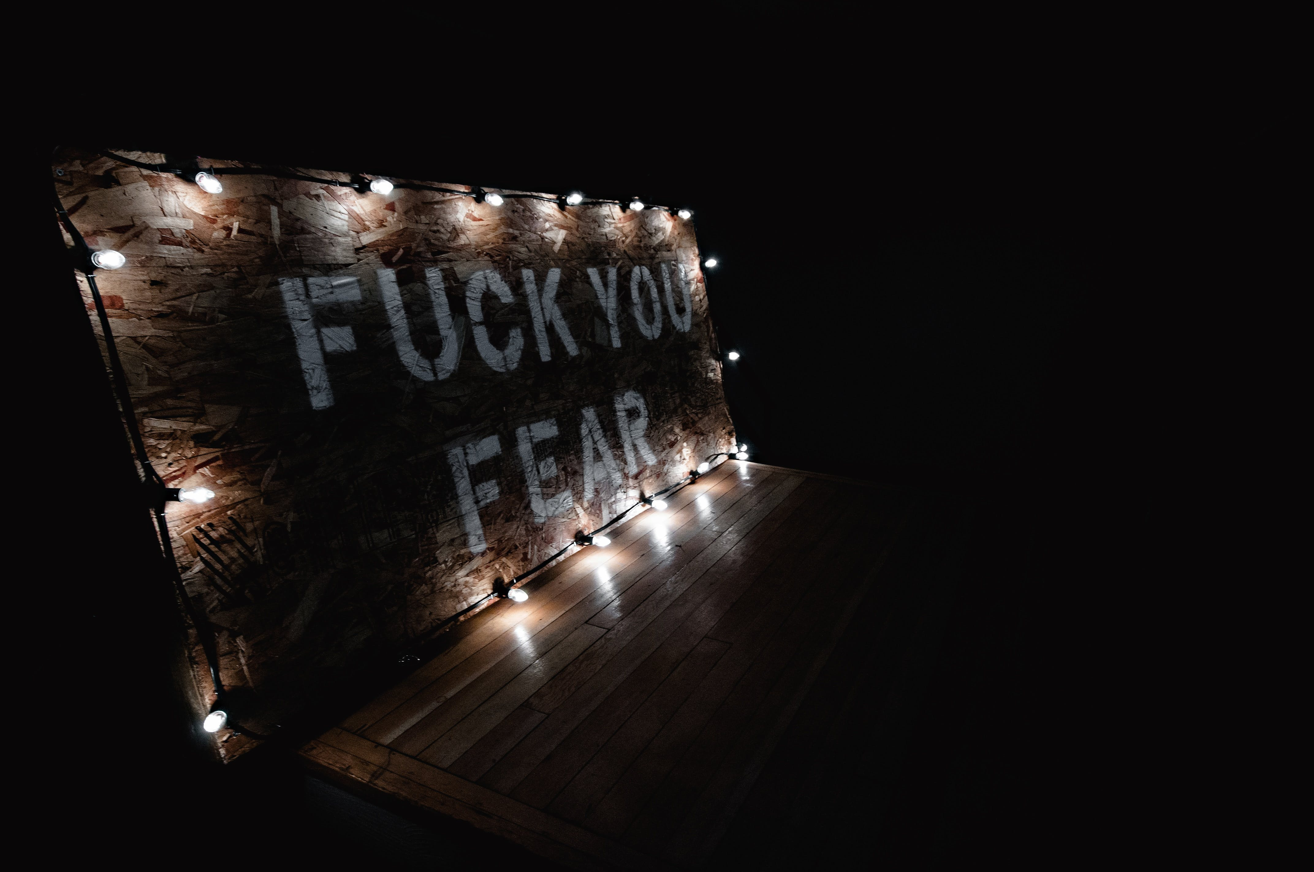 Fuck You Fear Text on Brown Wooden Wall