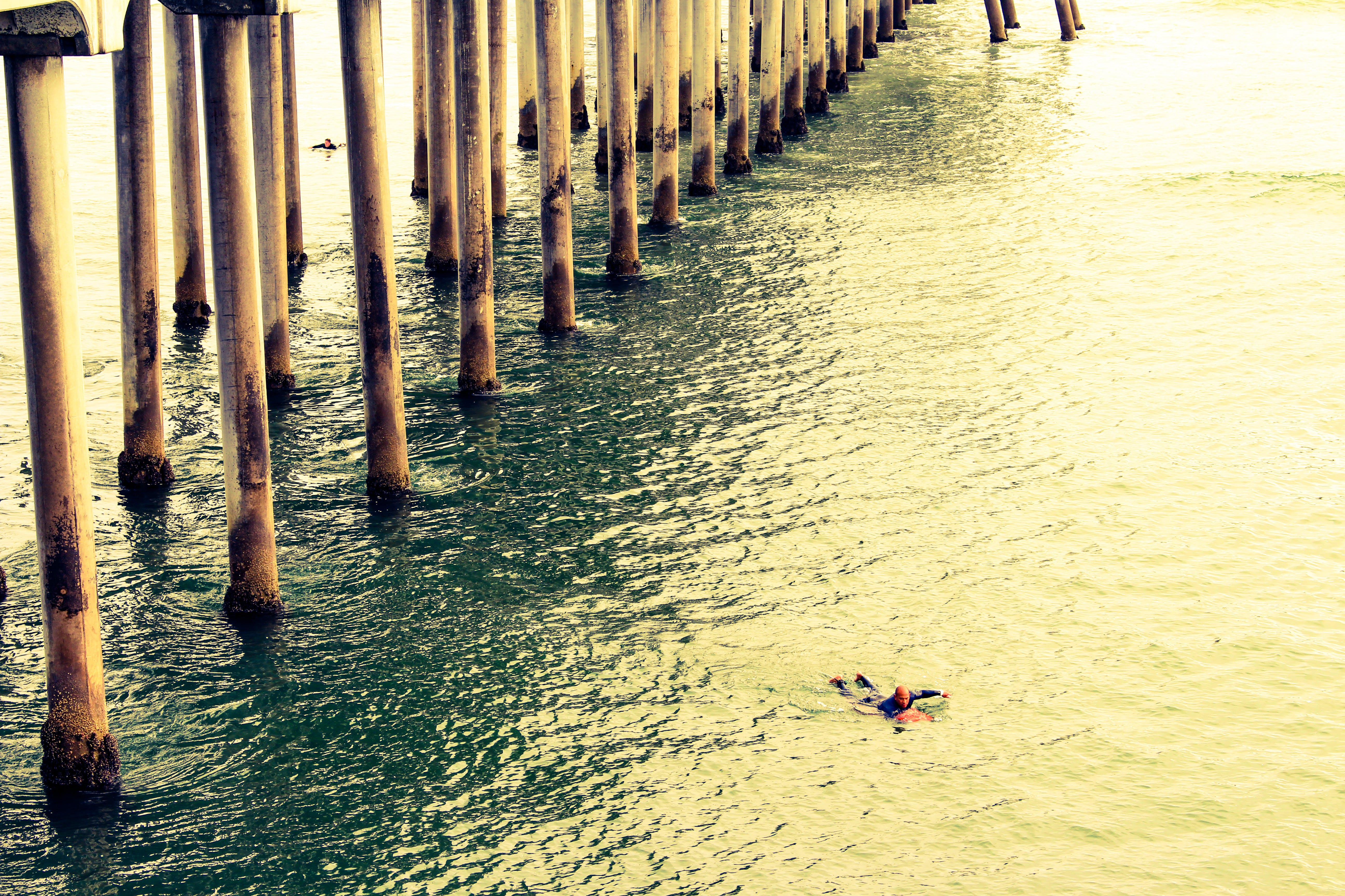 Person Swimming on Body of Water Near Wooden Columns