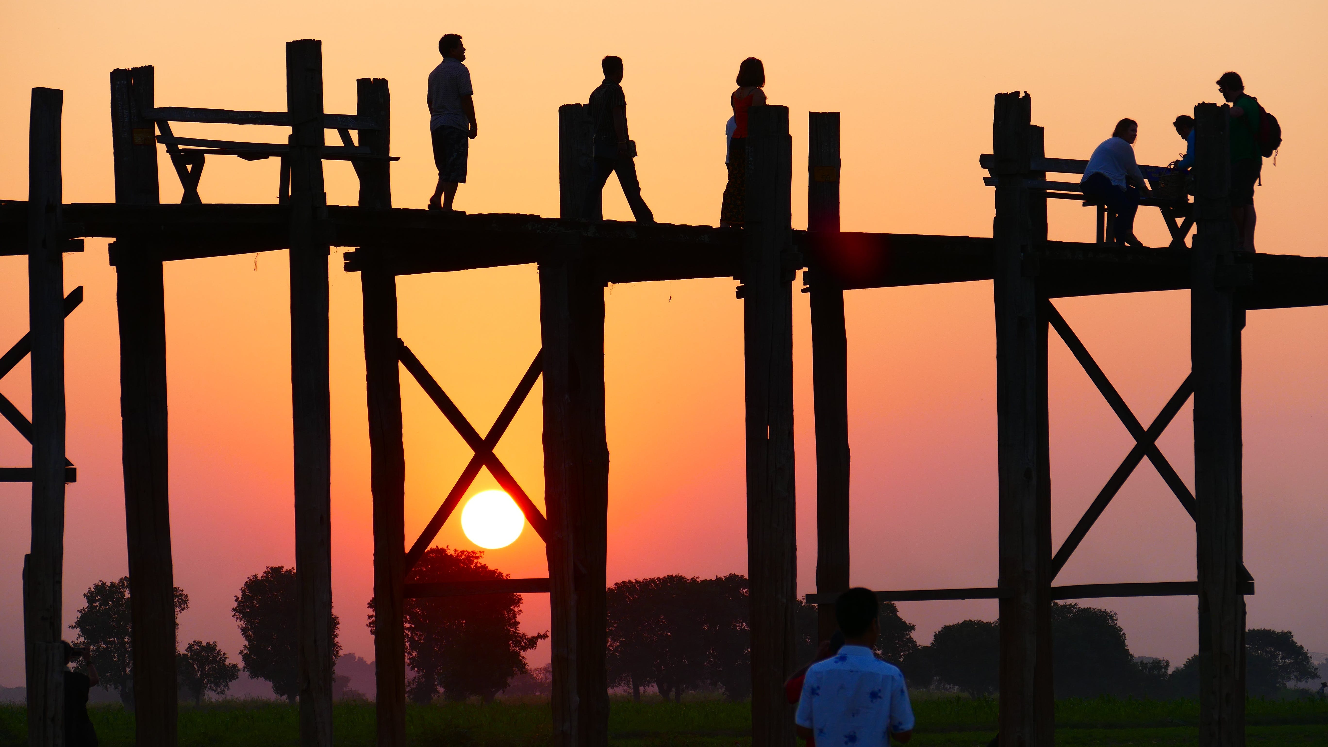 People Standing on a Bridge during Sunset .