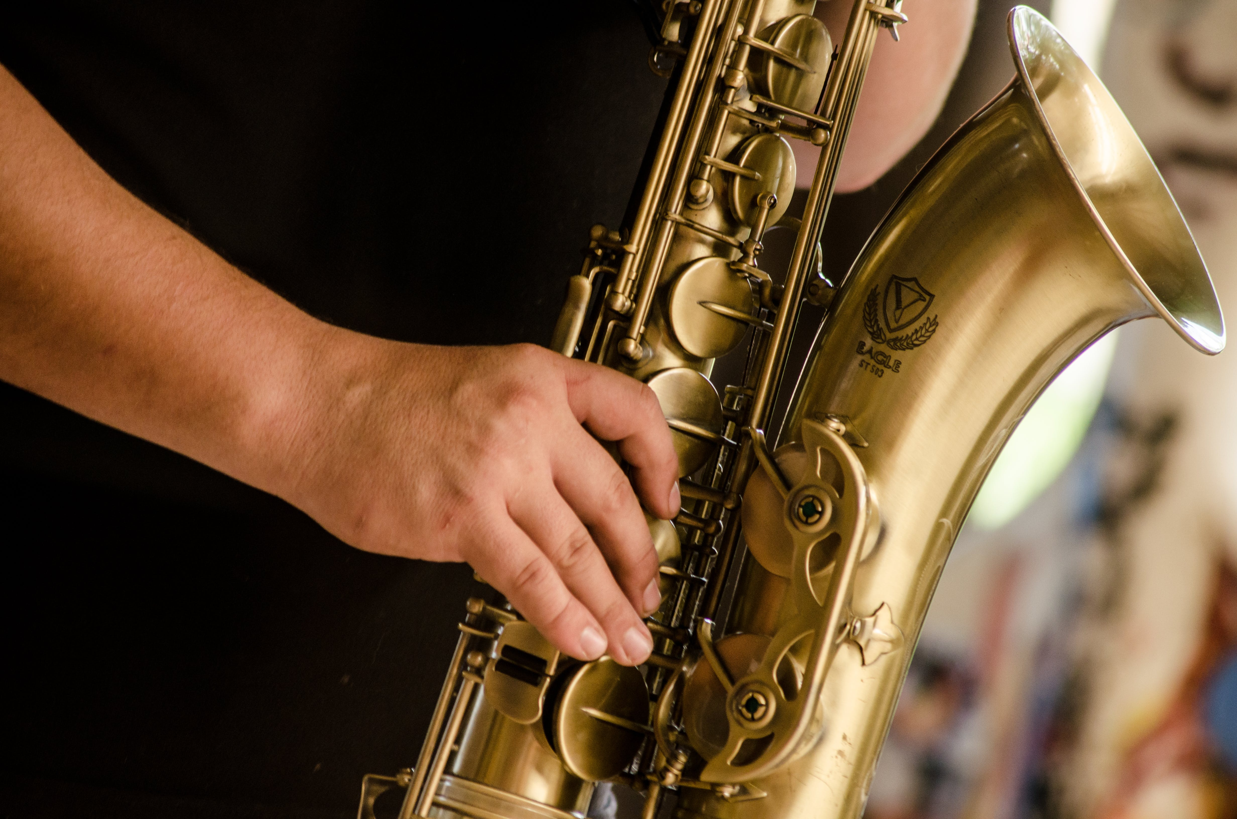Person in Black Shirt Playing Brass-colored Saxophone