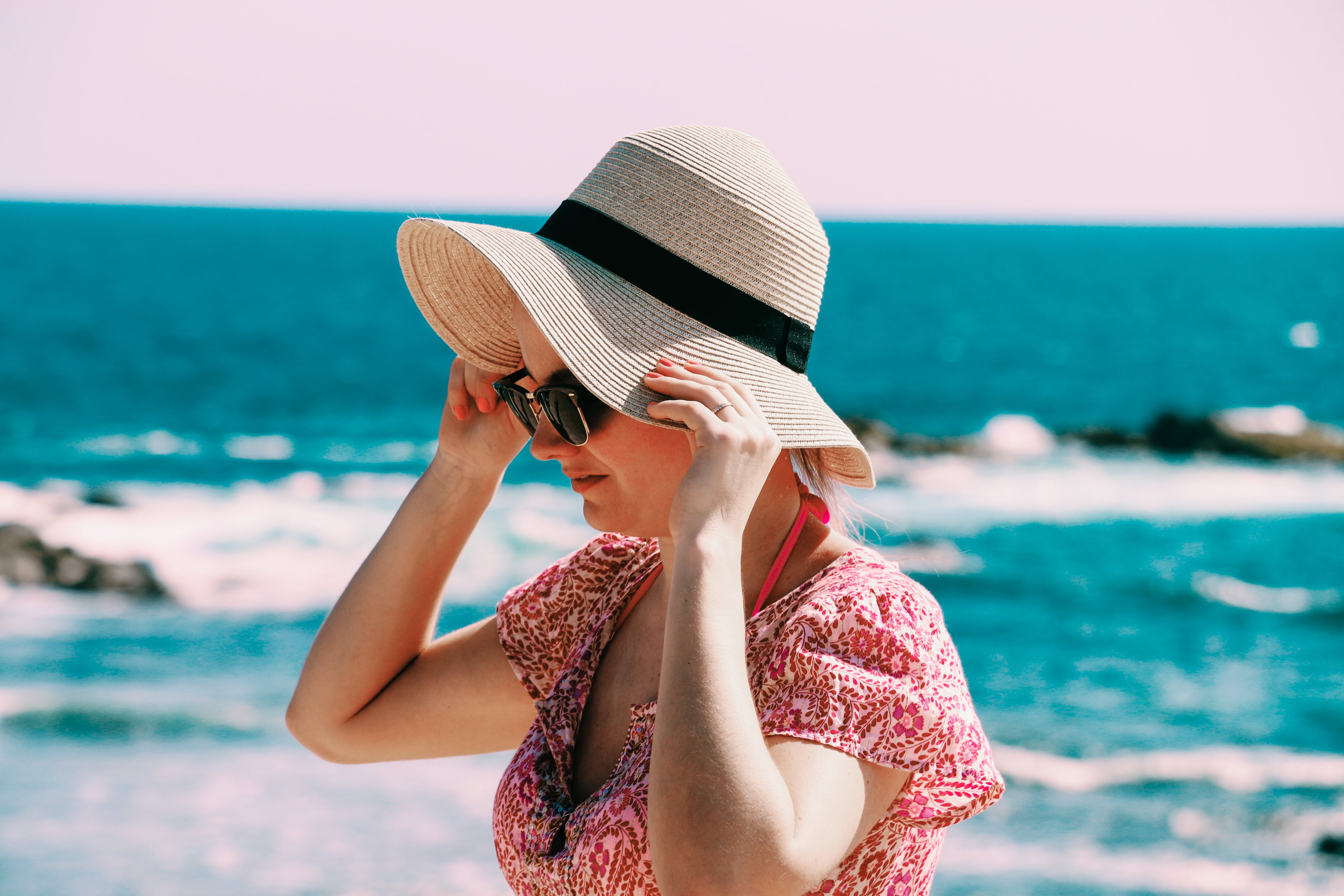 Selective Focus Photo of Woman Wears Beige Sun Hat Stand Behind Body of Water a Daytime