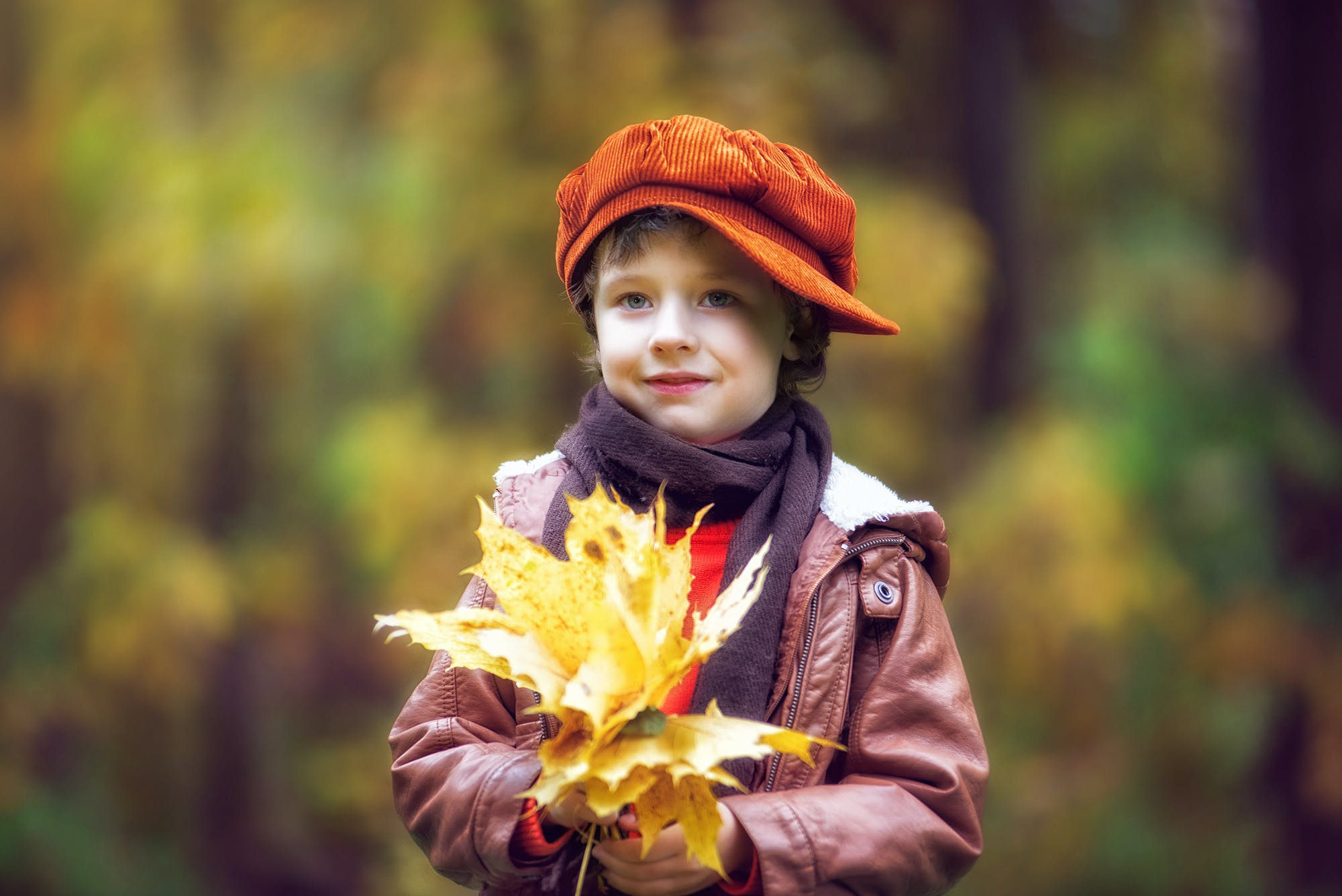 Boy Wearing Brown Leather Jacket Holding Yellow Leaves