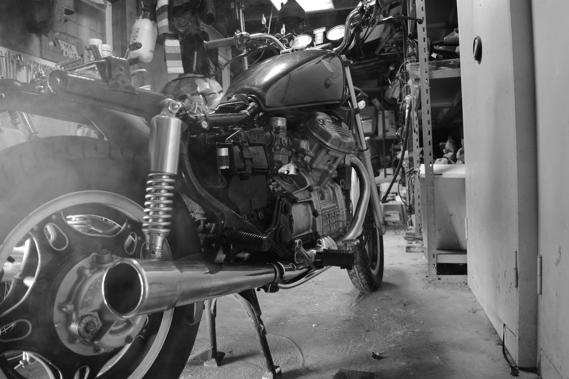 Grey and Black Cafe Racer Near White Wall in Grayscale