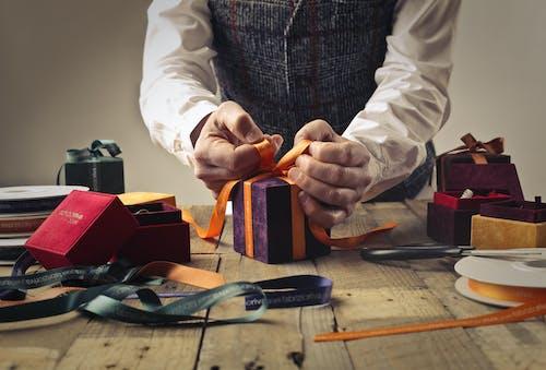 Person Tying Ribbon on Purple Gift Box