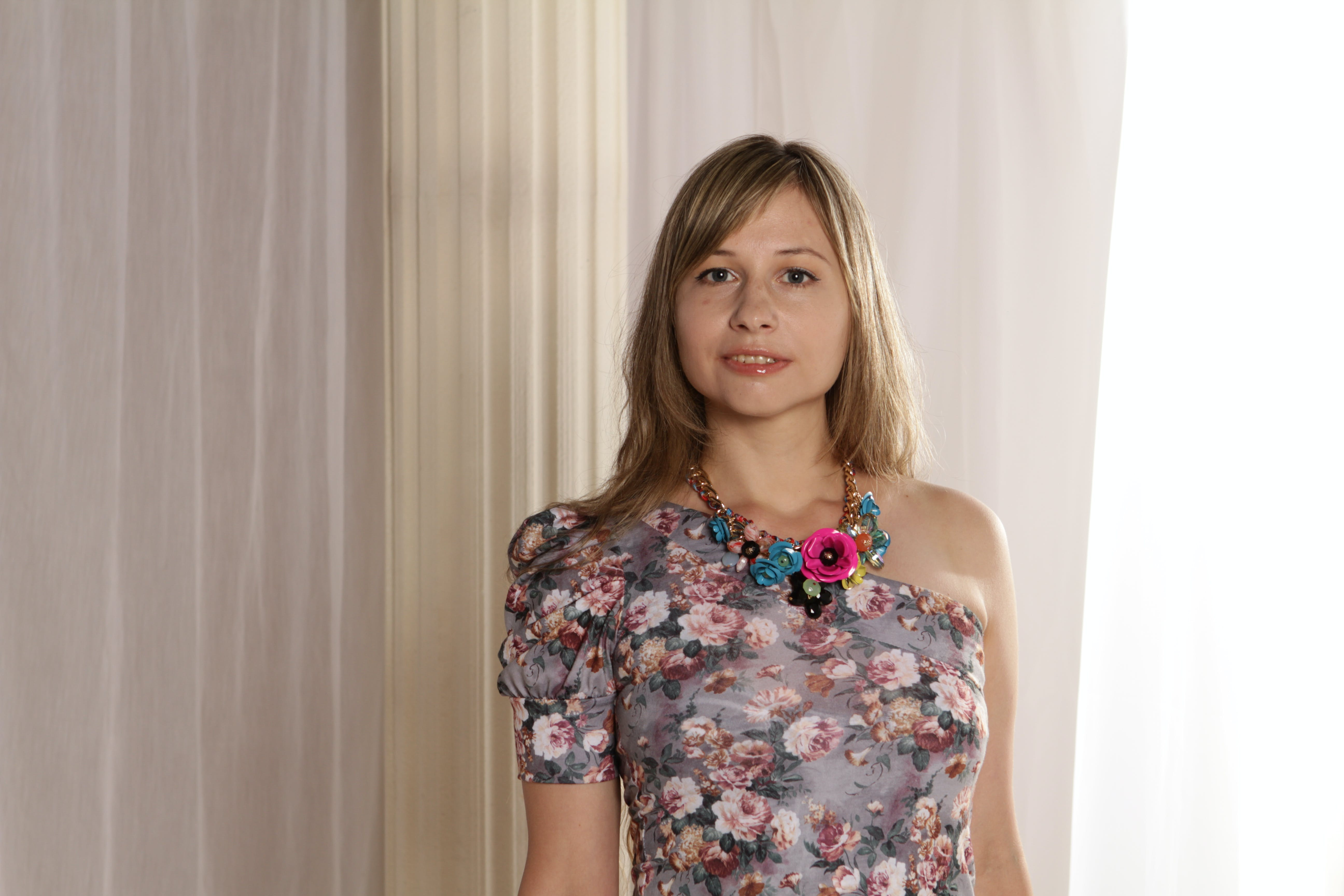 Woman Wearing Grey and Multicolored Floral Single-shoulder Top Against Beige Curtains