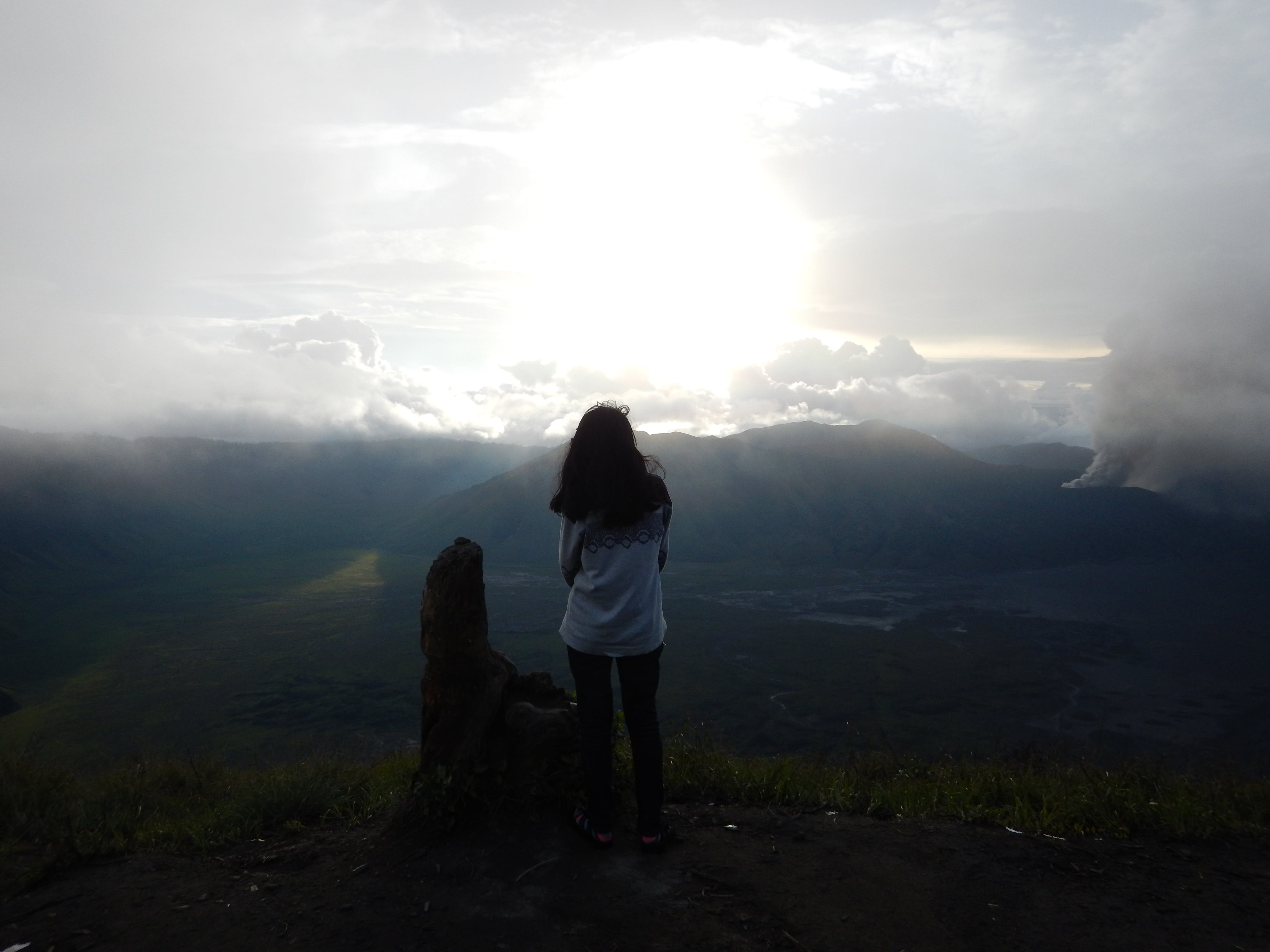 Woman Staing at the Edge of the Mountain Facing the Sun