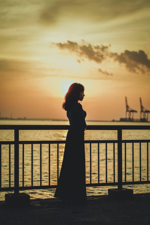 Silhouette Photo of Woman Near Railing