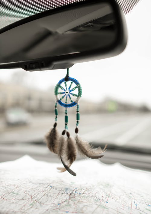 Small dreamcatcher hanging in car serving as mirror charm