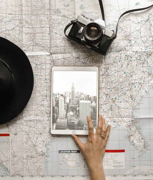 Flat Lay Photography of Person Touching Silver Ipad on World Map Chart Beside Black Hat
