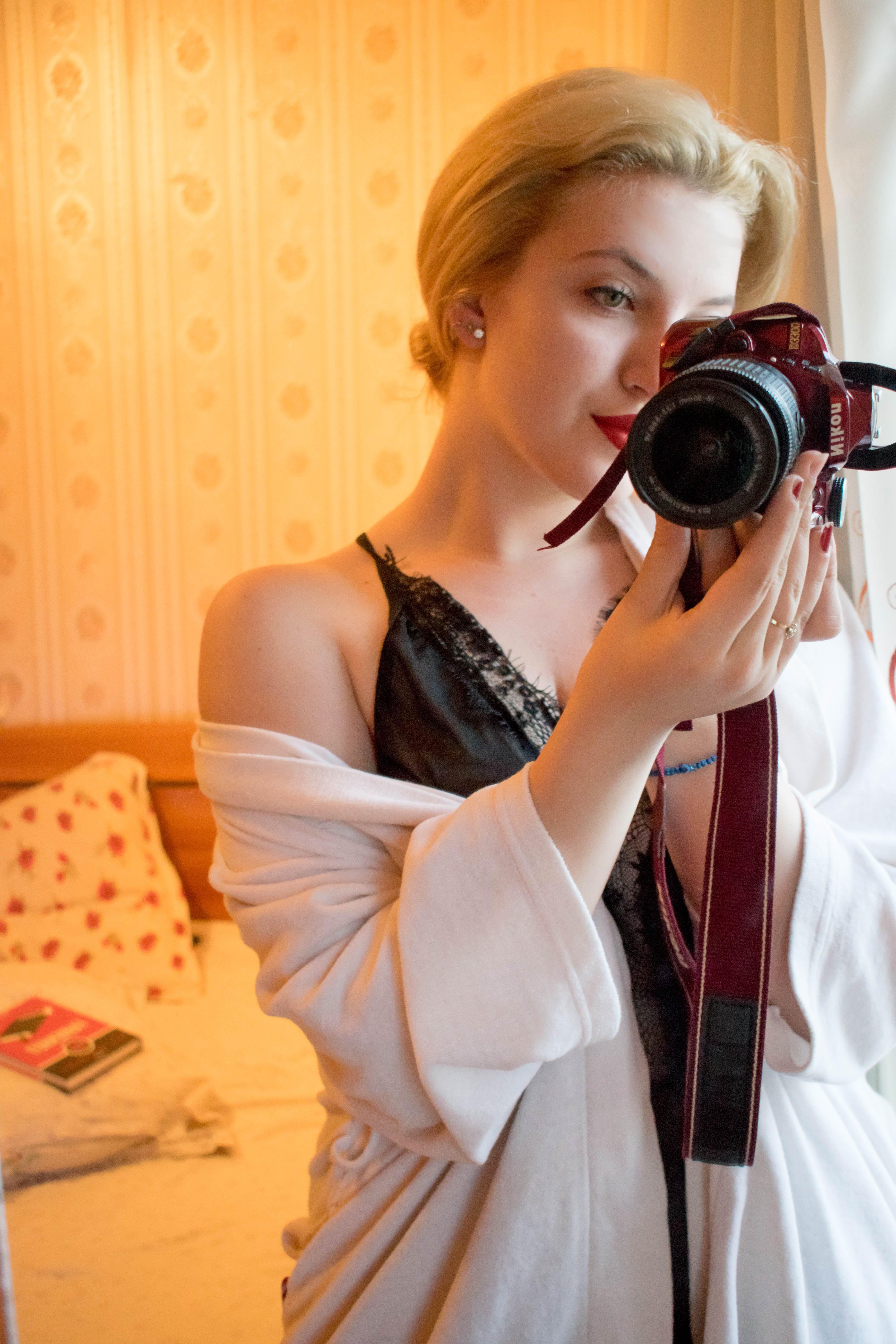 Woman Wearing Black Lace Floral Spaghetti Strap Dress Holding Black and Red Samsung Bridge Camera in Room