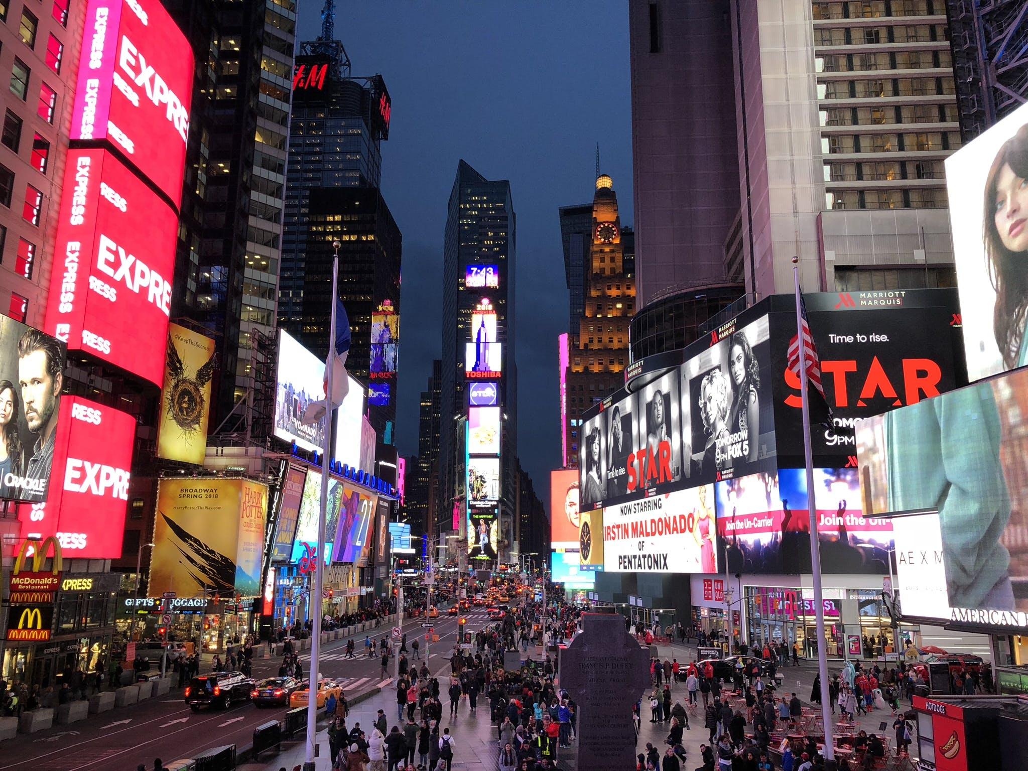 Crowd Walking Between Lighted Buildings during Nighttime