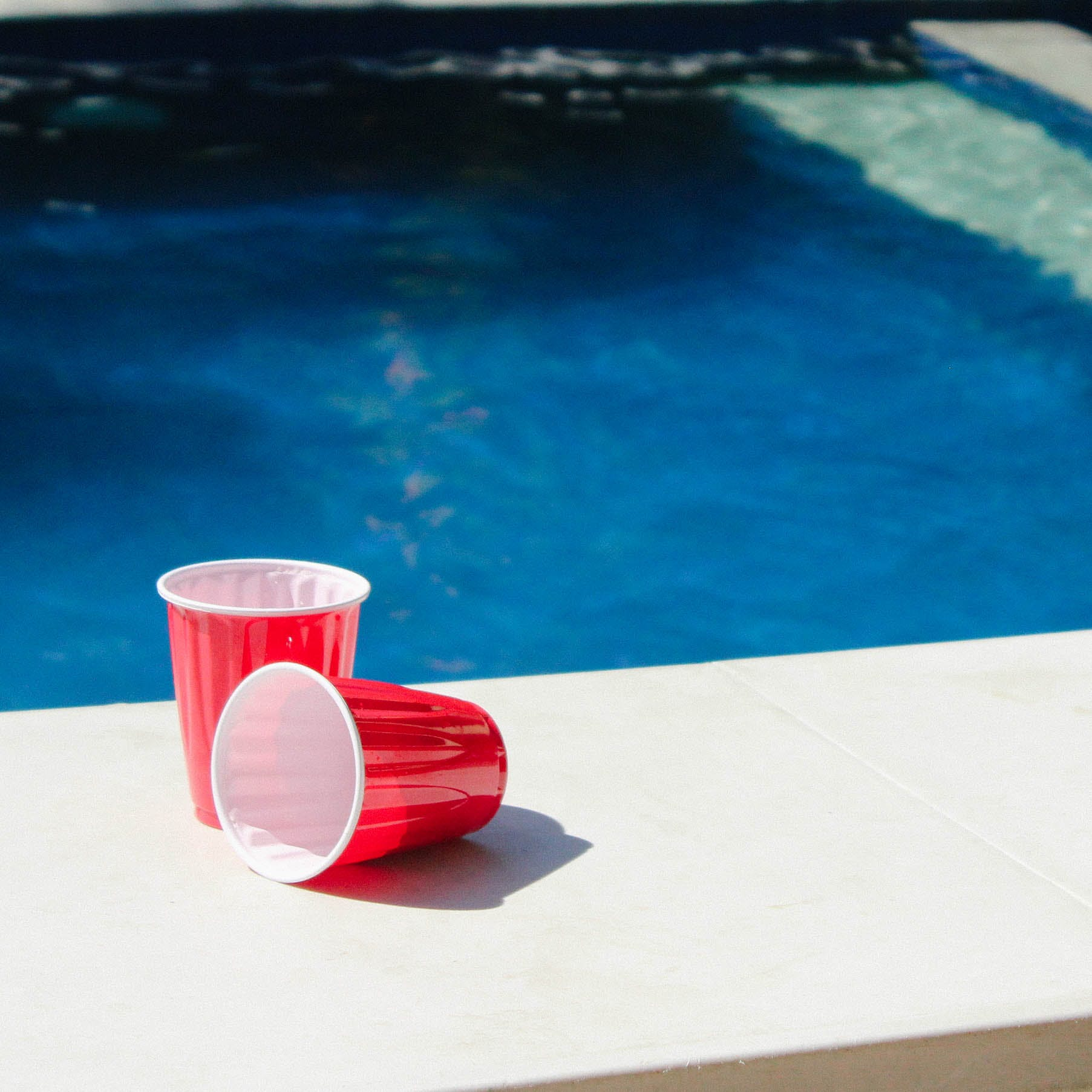 Two Red-and-white Disposable Cups on Gray Ceramic Tiles Photo