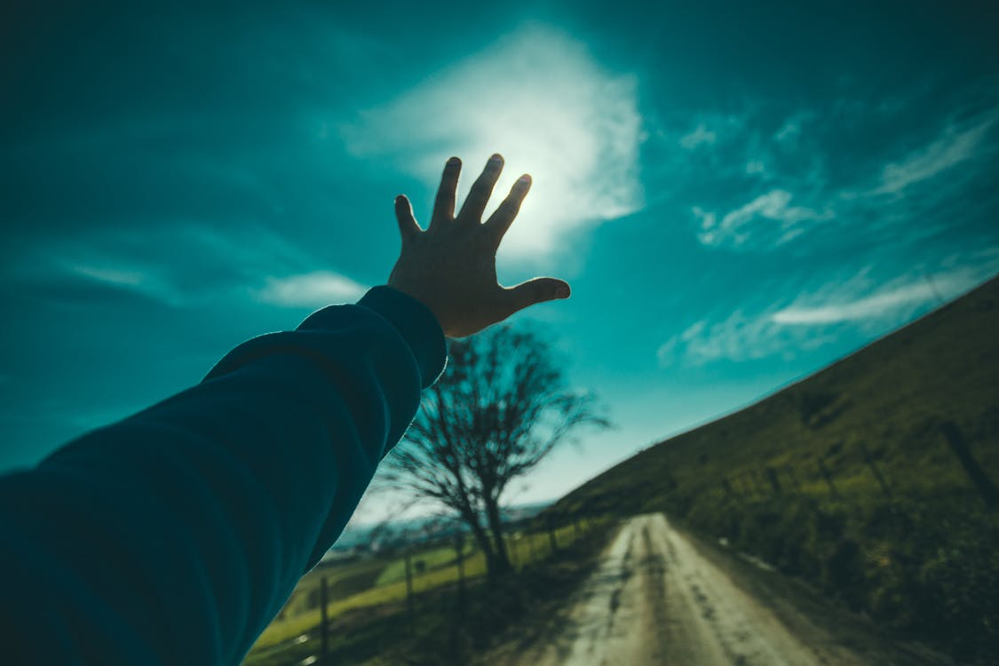 Person Raising Hand Towards Blue Sky during Daytime